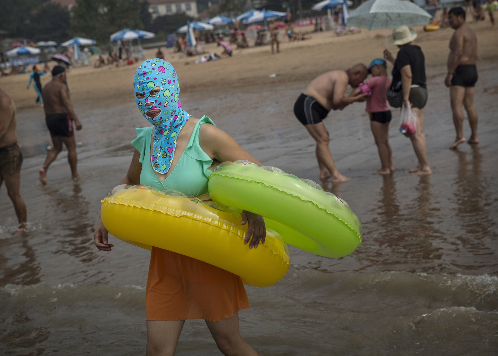 A woman wears a facekini as she walks into the water to swim on the beach on Aug. 22, 2014, on the Yellow Sea in Qingdao.