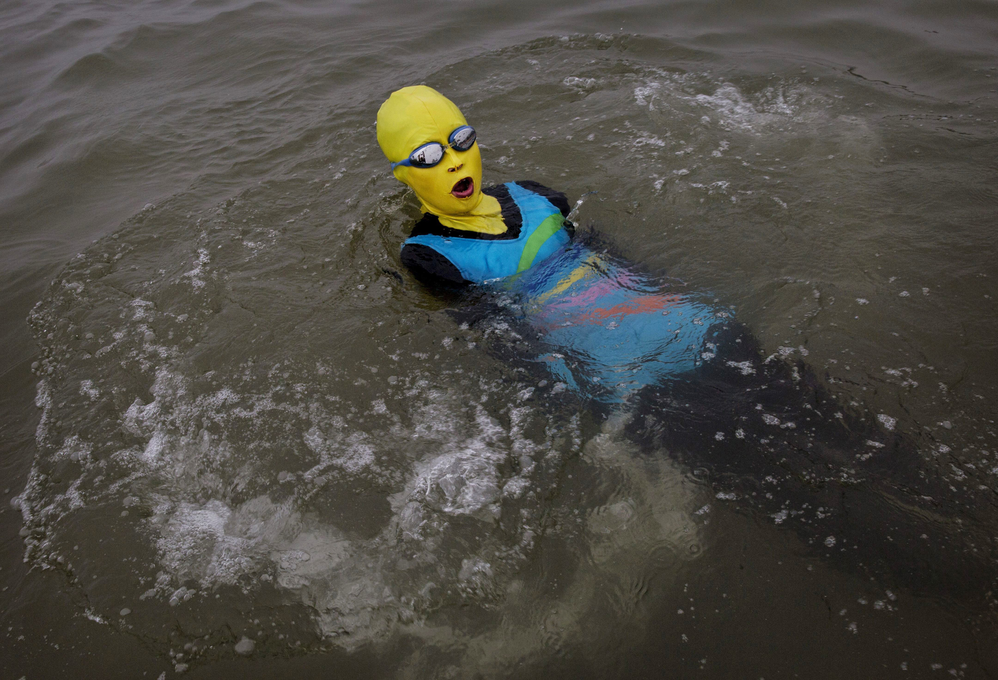 A woman wears a facekini as she swims on Aug. 20, 2014, on the Yellow Sea in Qingdao.
