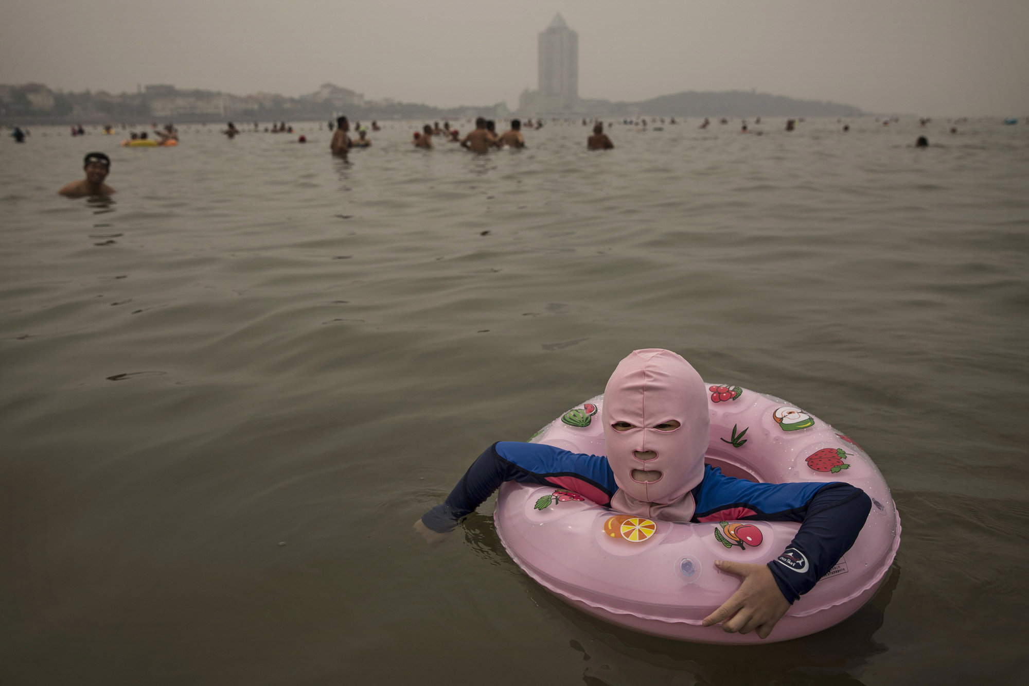 A girl wears a facekini as she floats in the water on Aug. 21, 2014, on the Yellow Sea in Qingdao.