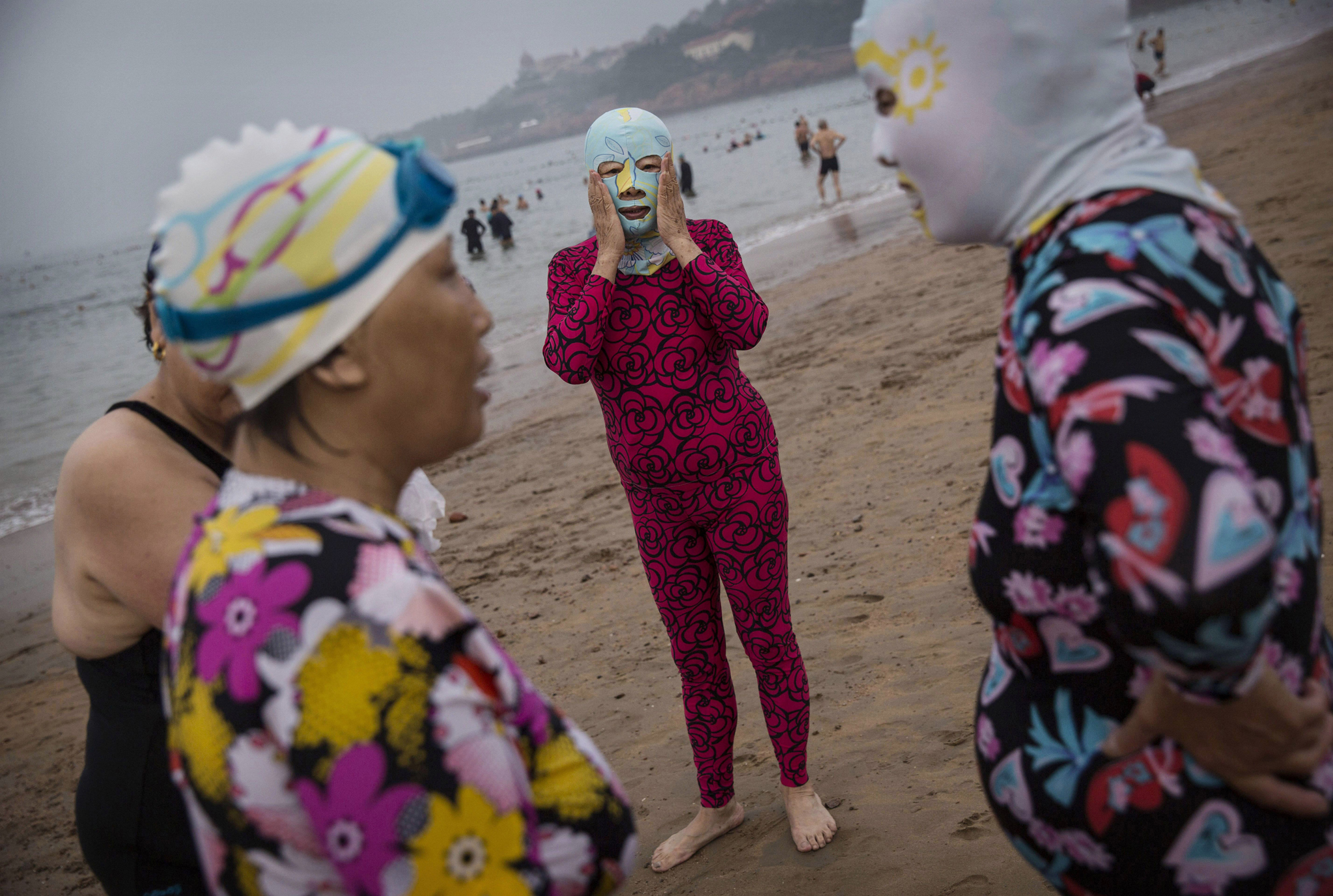 A woman adjust her facekini as she talks with others as they stand on the beach on Aug. 21, 2014, on the Yellow Sea in Qingdao.