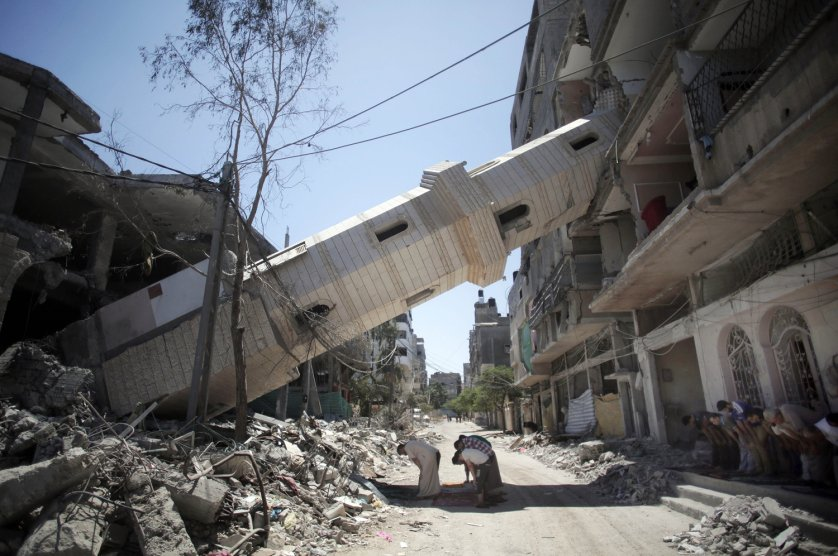 Aug. 8, 2014. Palestinians attend Friday noon prayers in the shadow of a toppled minaret at a mosque in Gaza City.