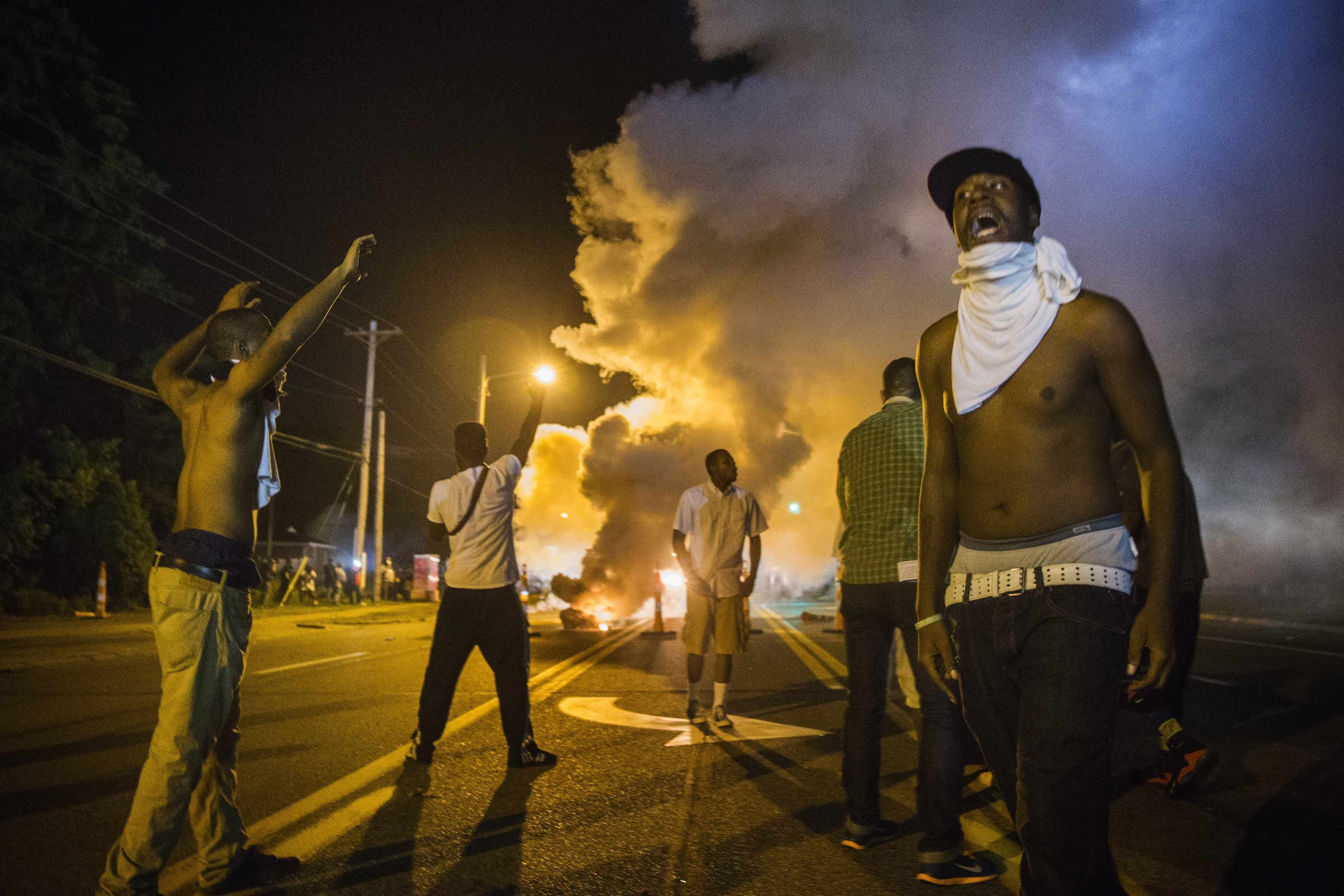 Demonstrators stand in the middle of West Florissant as they react to tear gas fired by police during ongoing protests in reaction to the shooting of teenager Michael Brown, near Ferguson, Missouri, August 18, 2014.