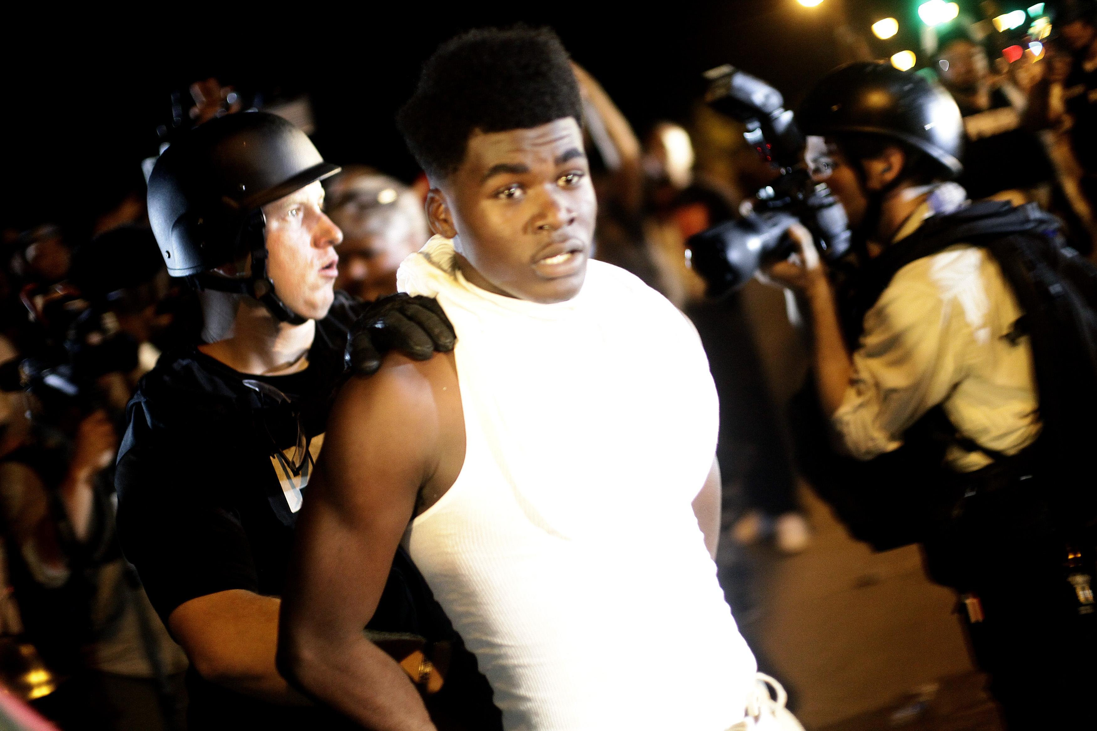 A police officer in riot gear detains a demonstrator protesting against the shooting of Michael Brown, in Ferguson, Mo. on Aug. 19, 2014.