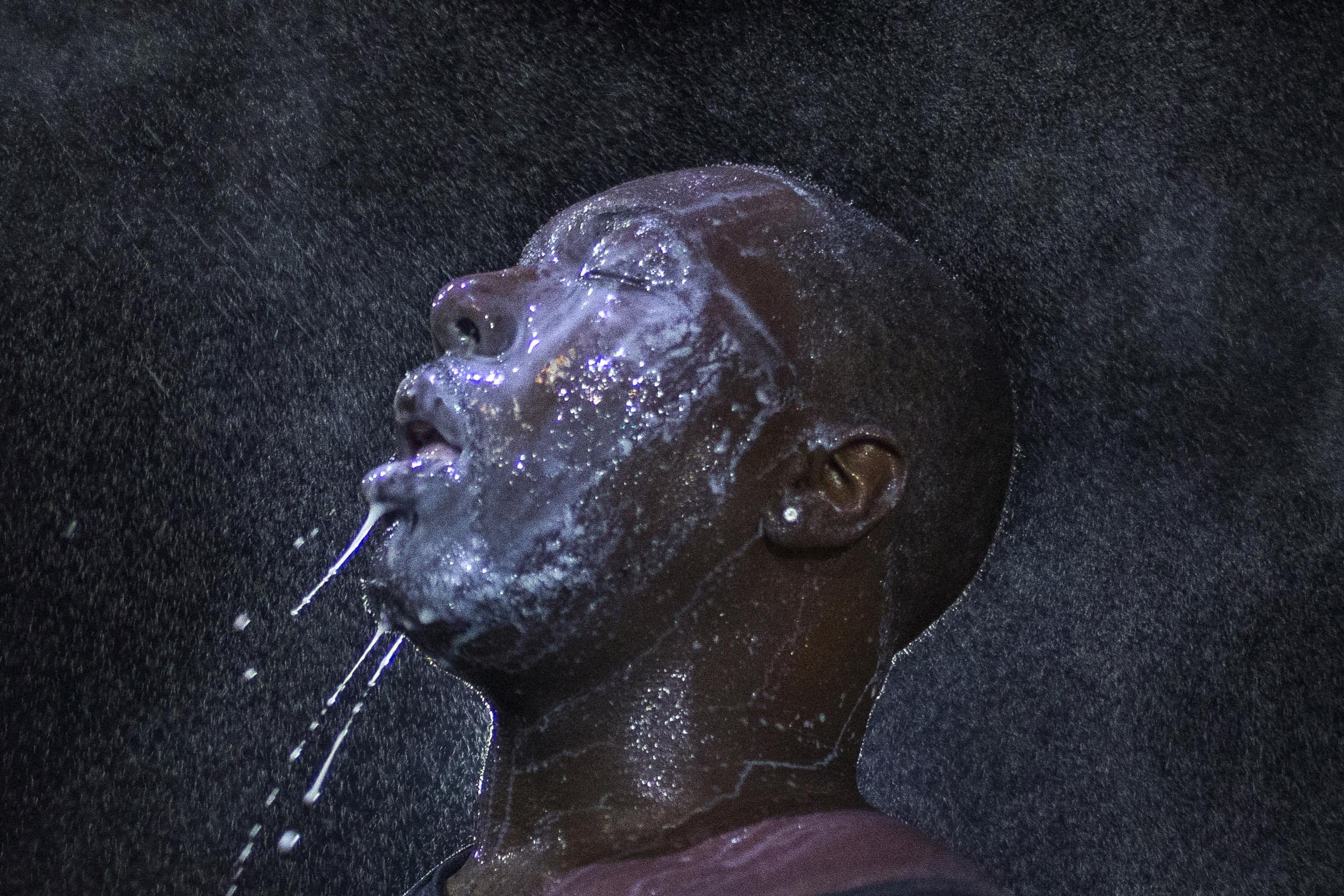 A man is doused with milk and sprayed with mist after being hit by an eye irritant from security forces trying to disperse demonstrators in Ferguson, Mo. early on Aug. 20, 2014.