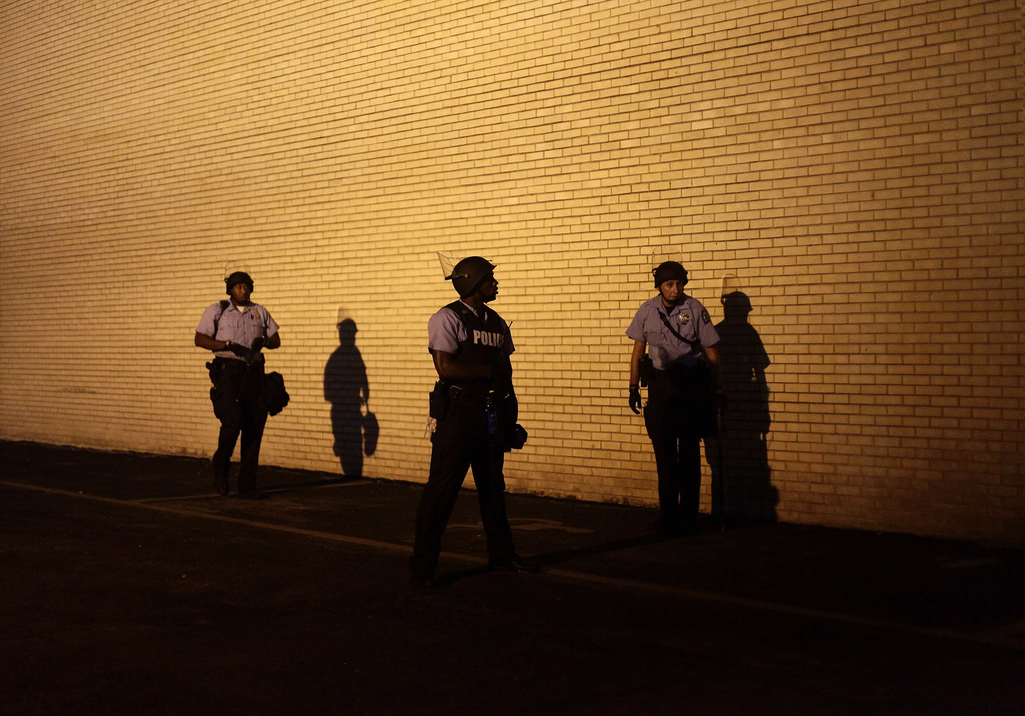 Police officers in riot gear watch demonstrators protesting against the shooting of Michael Brown from the side of a building in Ferguson, Mo. on Aug. 19, 2014.