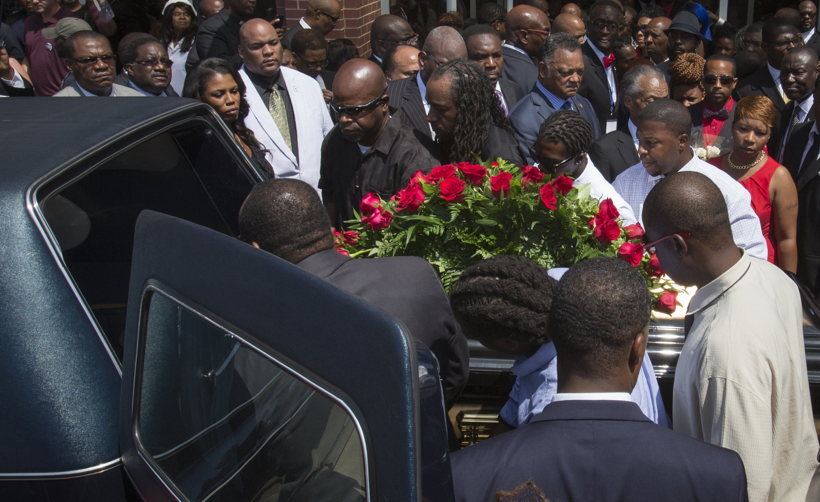 Lesley McSpadden (R, in red) watches as the casket containing the body of her son Michael Brown is lifted into a hearse after his funeral services at the Friendly Temple Missionary Baptist Church in St. Louis on Aug. 25, 2014.