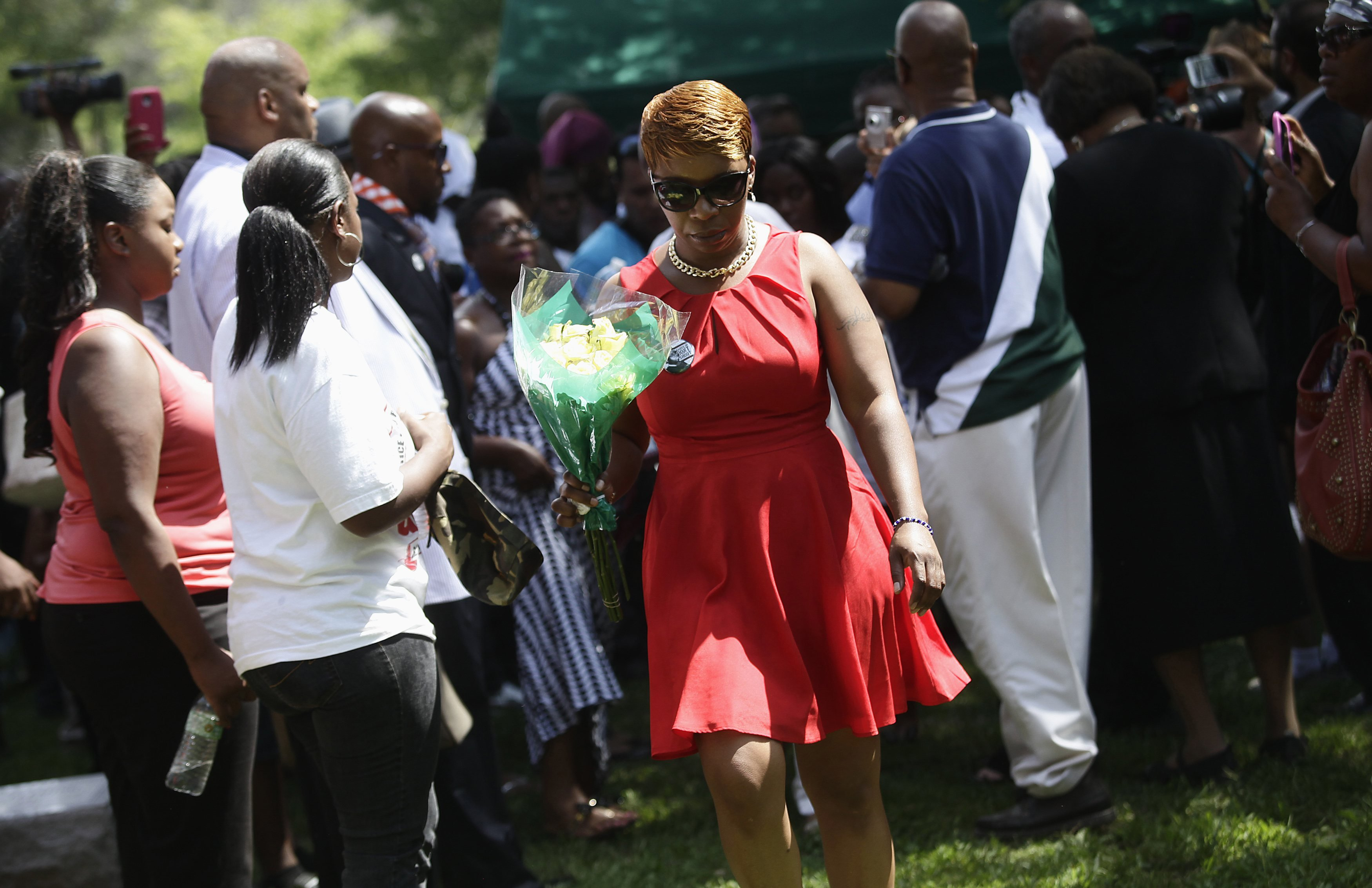 Lesley McSpadden (C) leaves the burial service for her son Michael Brown with a bouquet of flowers at St. Peter's Cemetery in St. Louis, on Aug. 25, 2014.