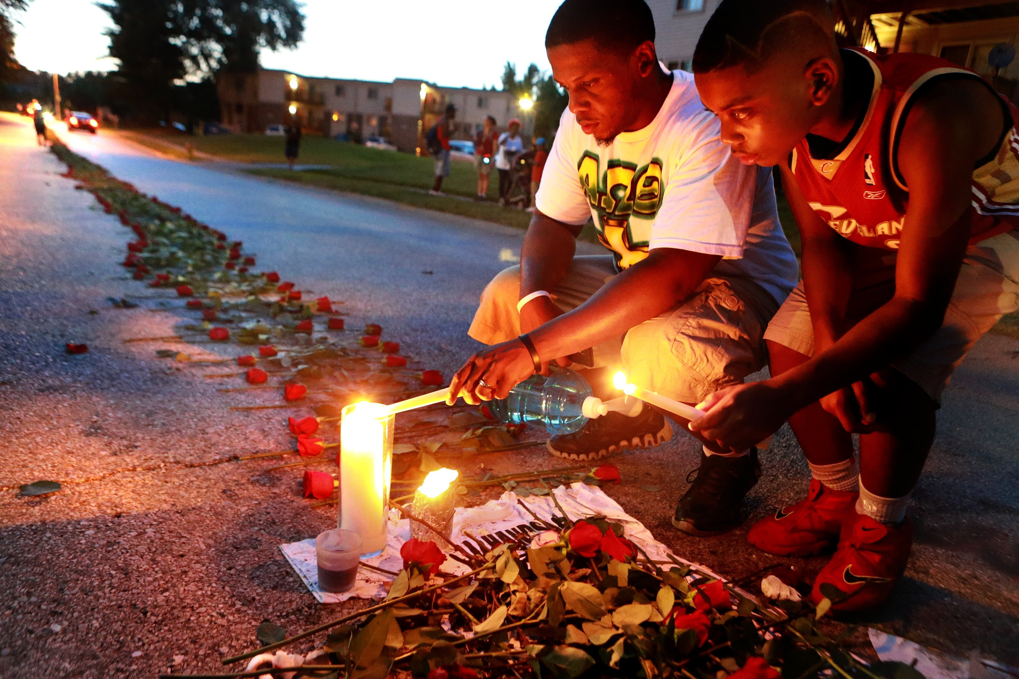 Theo Murphy (left) of Florissant and his brother Jordan Marshall light candles, at a memorial on Canfield Drive where unarmed teen Michael Brown was fatally shot, Aug. 21, 2014 in Ferguson, Mo.