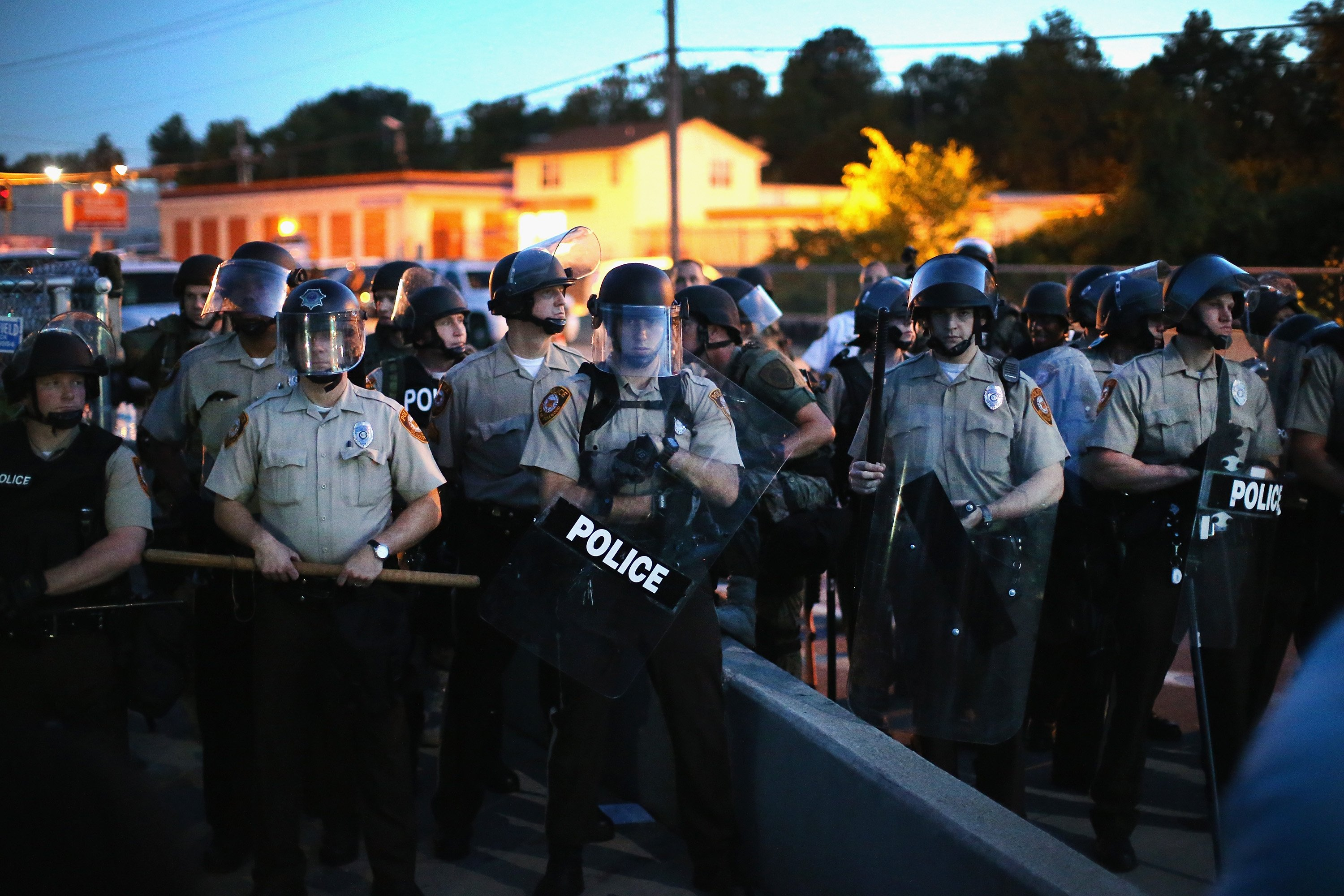 Police stand watch as demonstrators protest the shooting death of teenager Michael Brown in Ferguson, Mo. on Aug. 13, 2014.