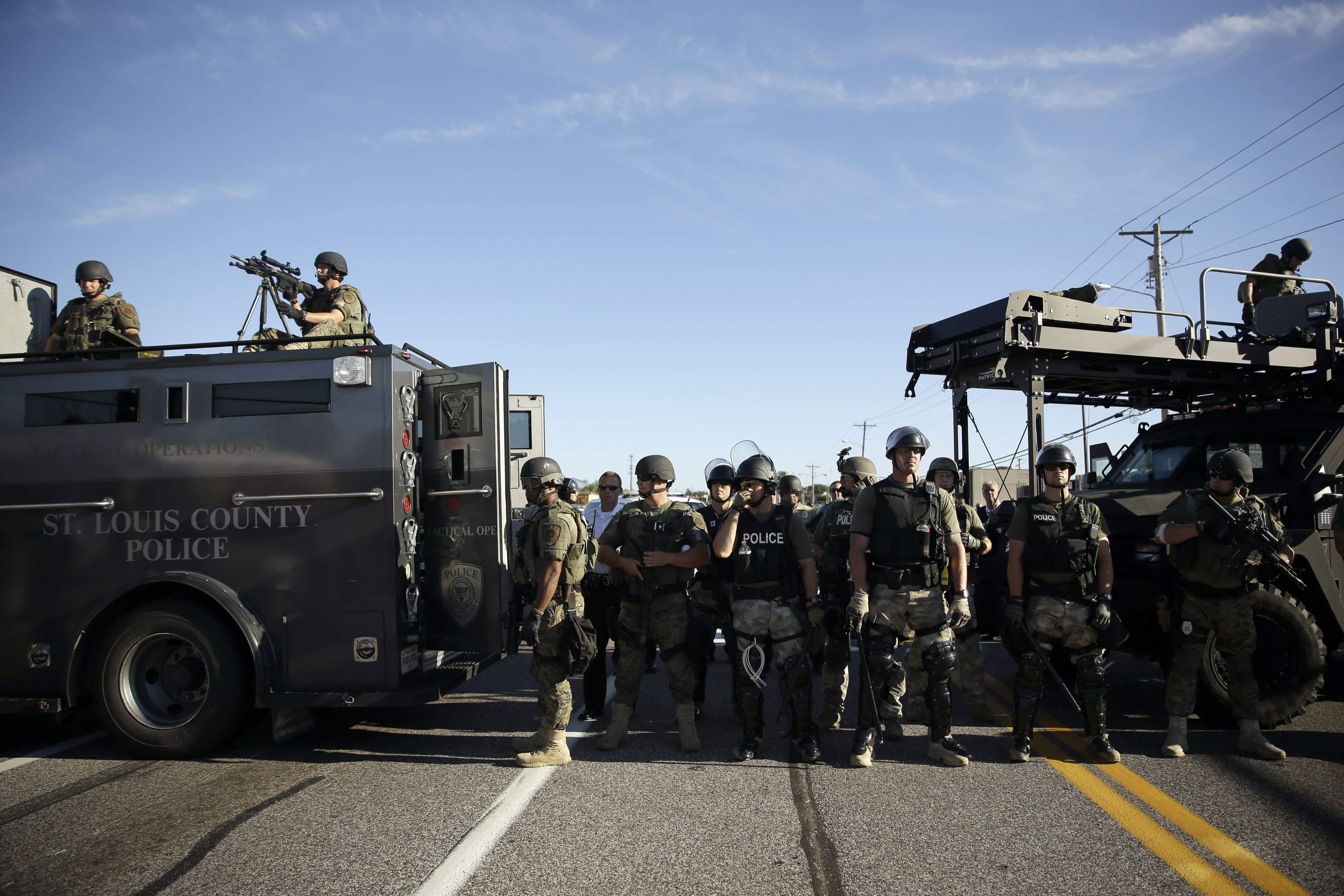 Police in riot gear watch protesters in Ferguson, Mo. on Aug. 13, 2014.
