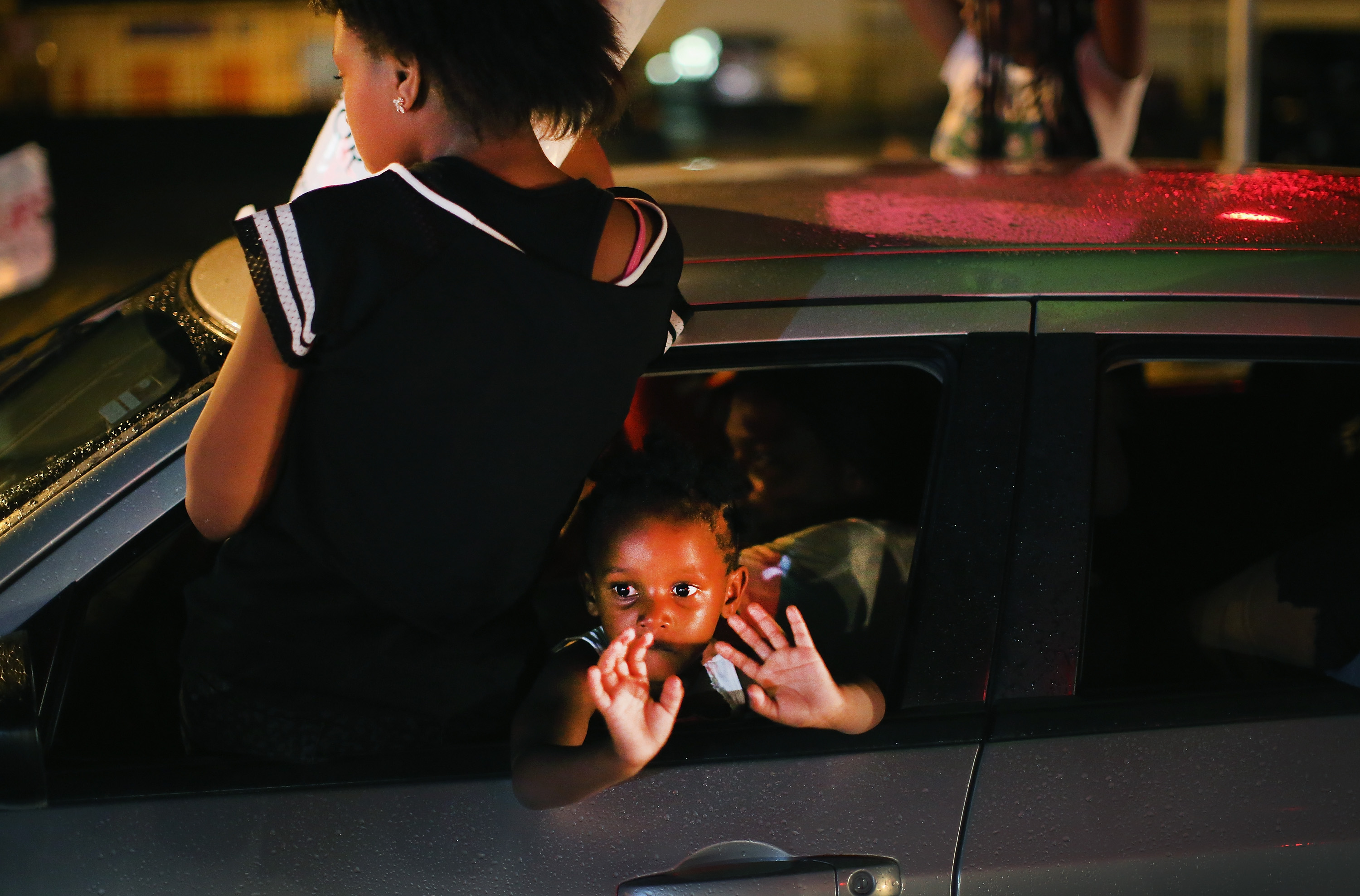 A young child looks out from a car as demonstrators drive down West Florissant Avenue protesting the shooting and death of Michael Brown in Ferguson, Mo. on Aug. 15, 2014.