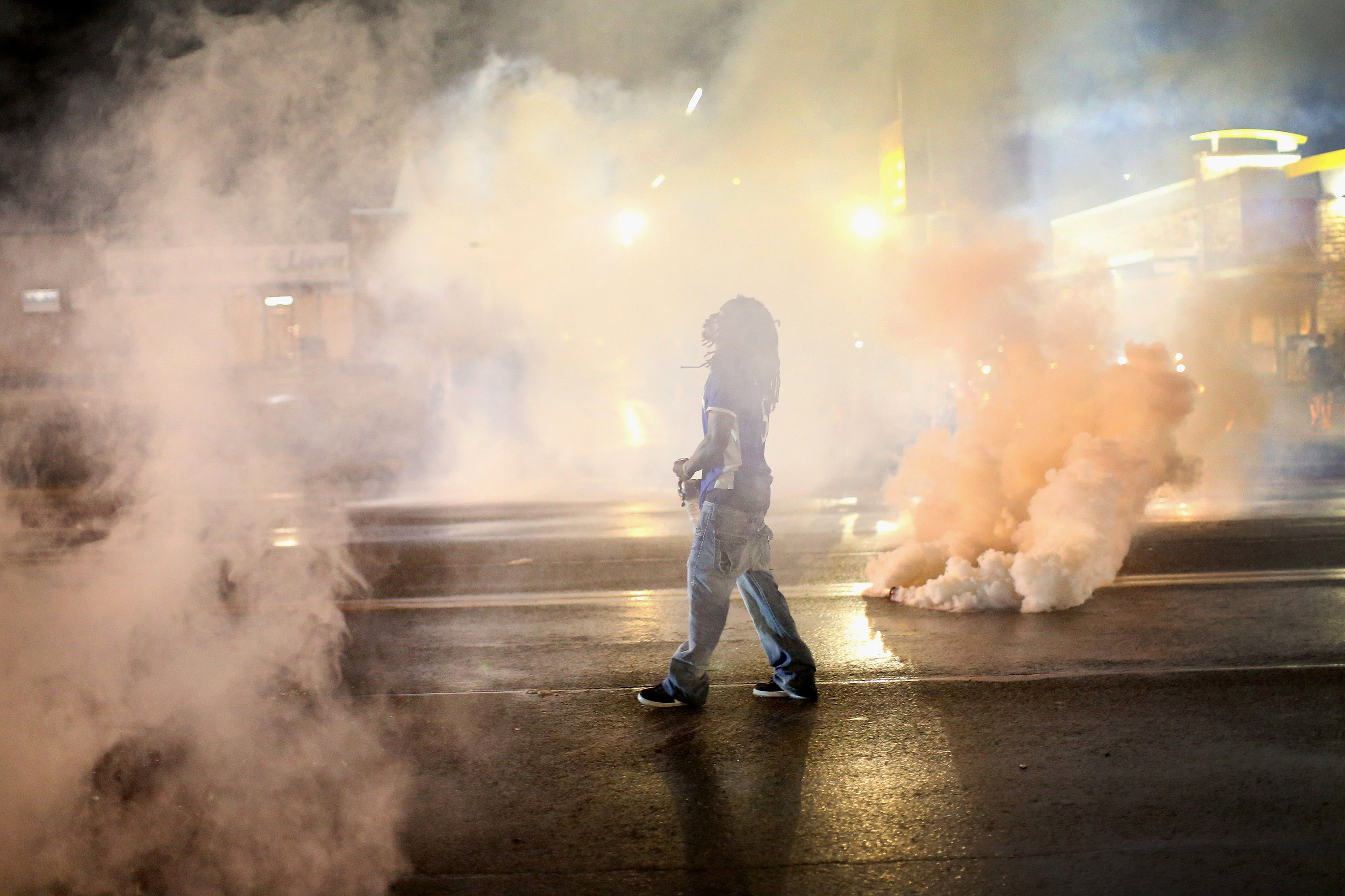 A demonstrator walks through smoke launched by police after a skirmish in Ferguson, Mo. on Aug. 15, 2014