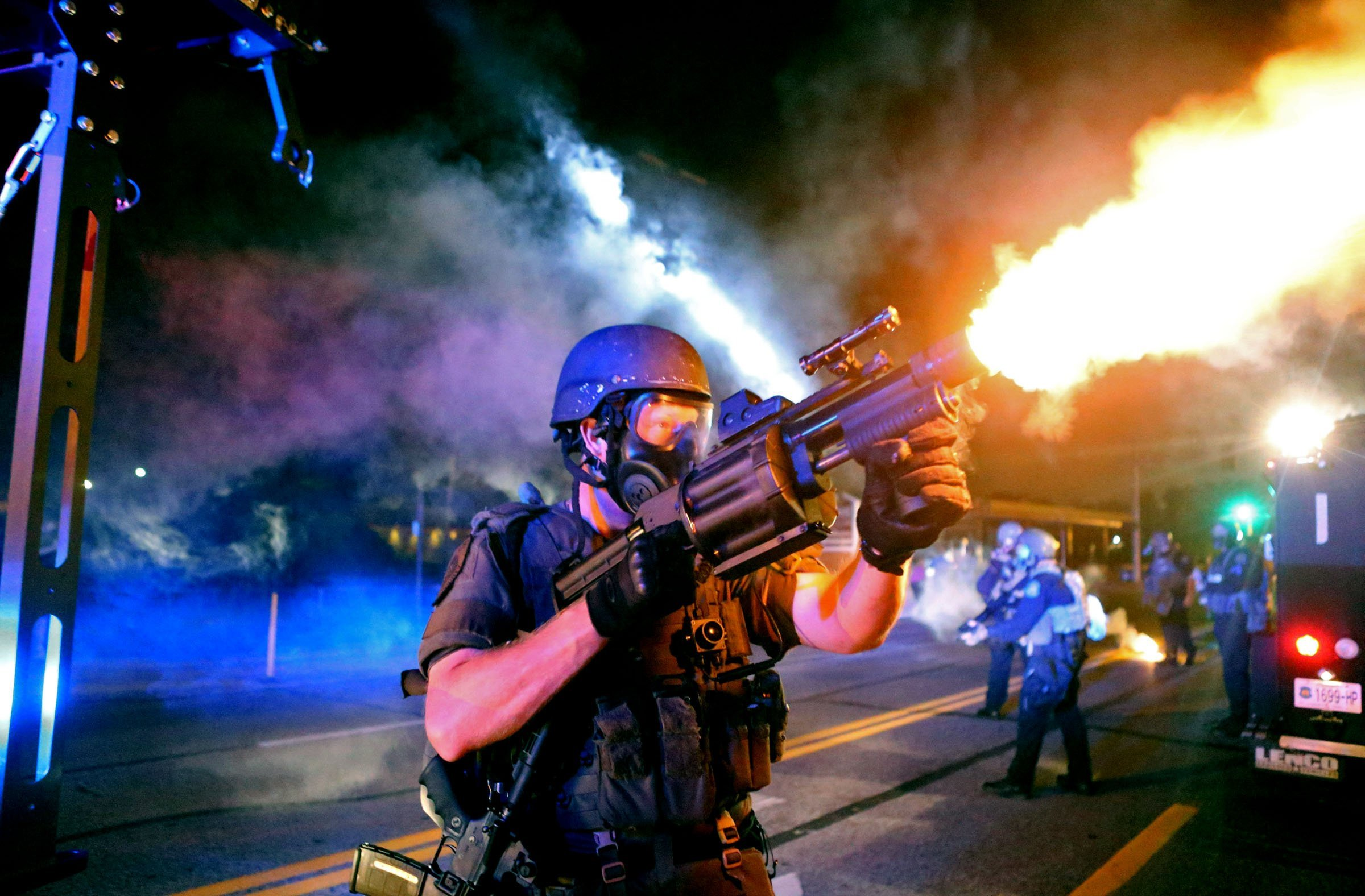 Police fire tear gas in the direction of where bottles were thrown from crowds gathered near the QuikTrip on W. Florissant Avenue in Ferguson, Mo. on Aug. 18, 2014.