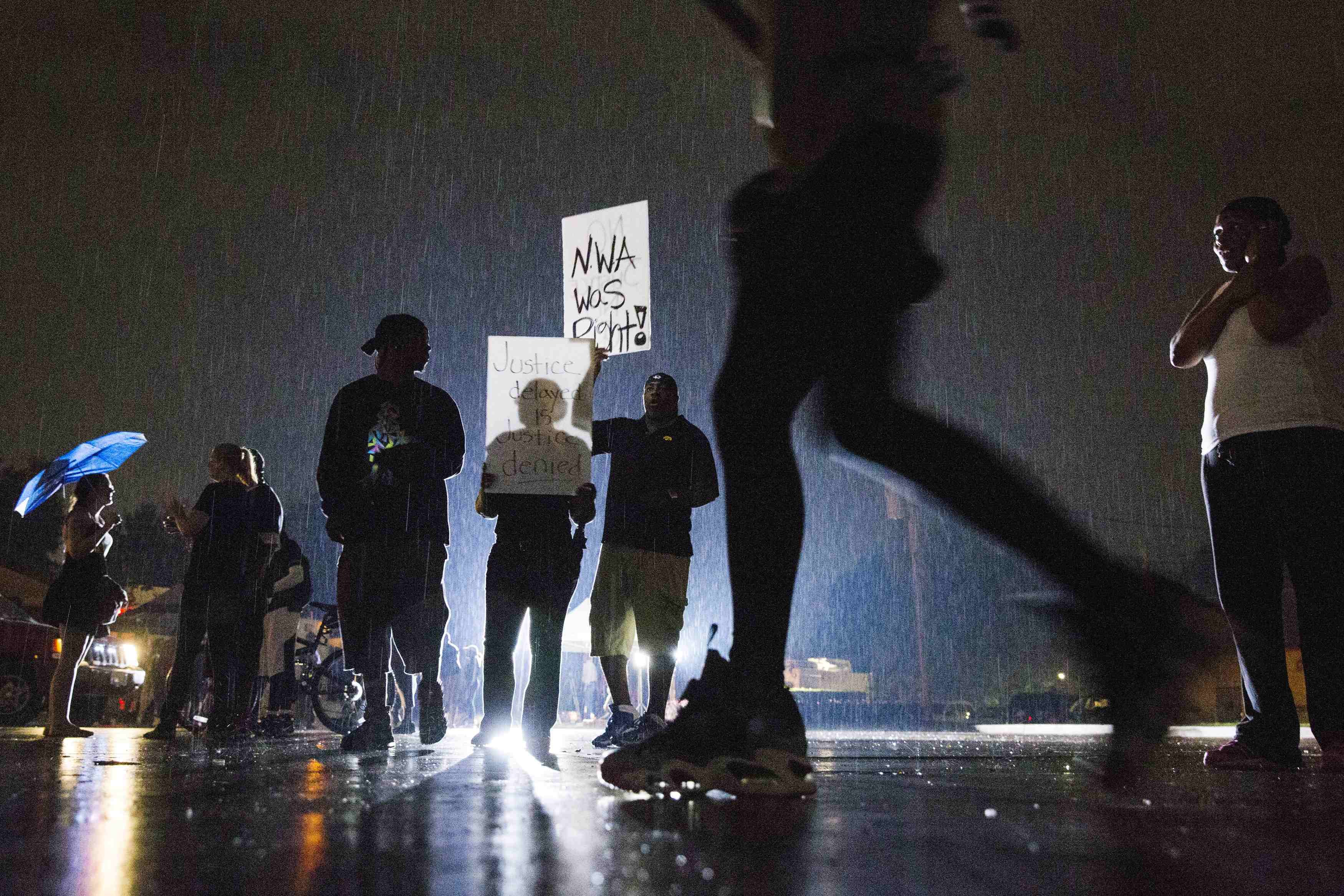 Protesters hold signs during a demonstration to protest the shooting of Michael Brown and the resulting police response in Ferguson, Mo. on Aug. 15, 2014.