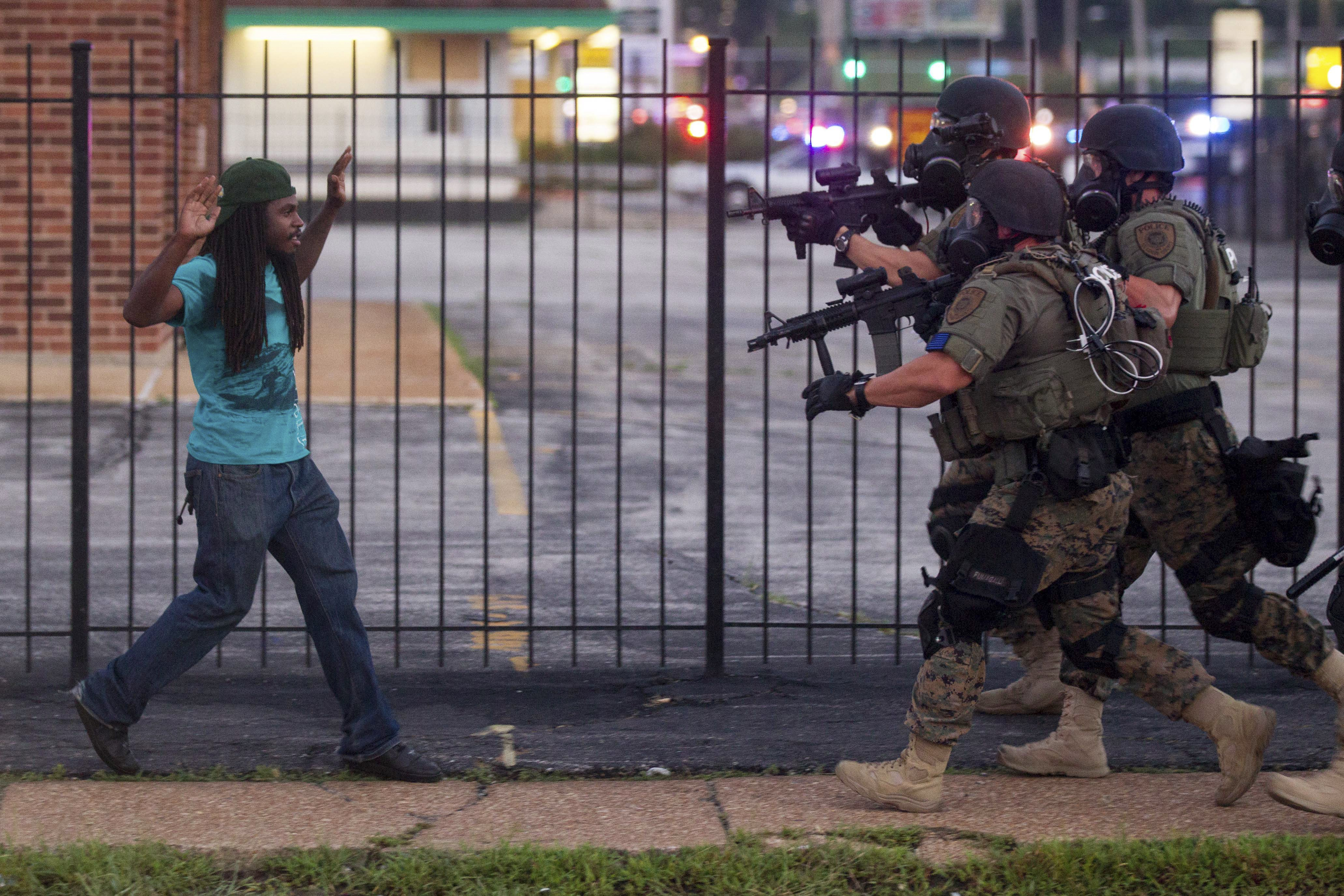 A man backs away as law enforcement officials close in on him and eventually detain him during protests over the death of Michael Brown, an unarmed black teenager killed by a police officer, in Ferguson, Mo., Aug. 11, 2014.