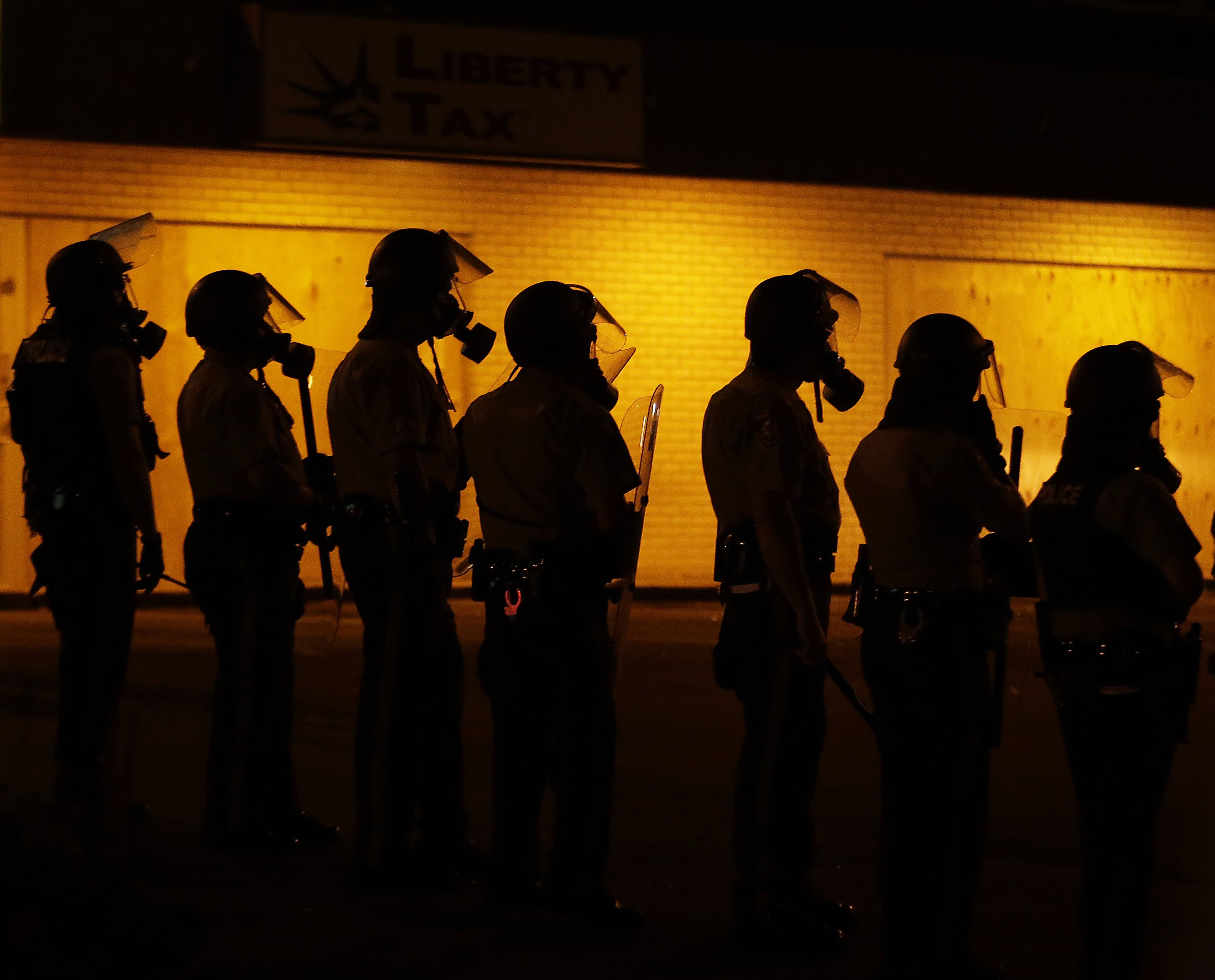 Police wait to advance after tear gas was used to disperse a crowd in Ferguson, Mo. on Aug. 17, 2014.