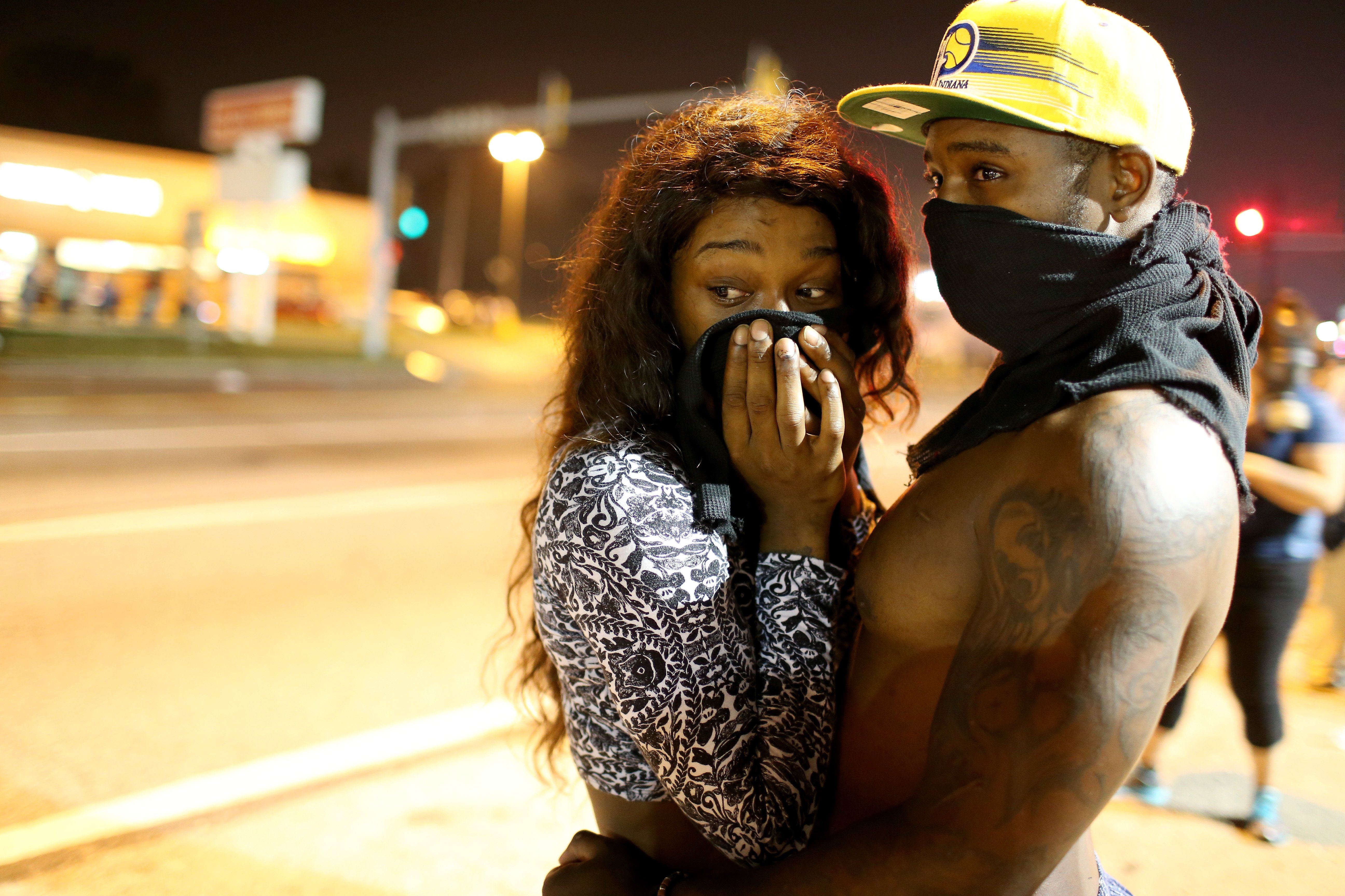 Demonstrators  cover their faces as tear gas fills the air as police fire the gas against an unruly crowd protesting the shooting death of Michael Brown in Ferguson, Mo. on Aug.18, 2014