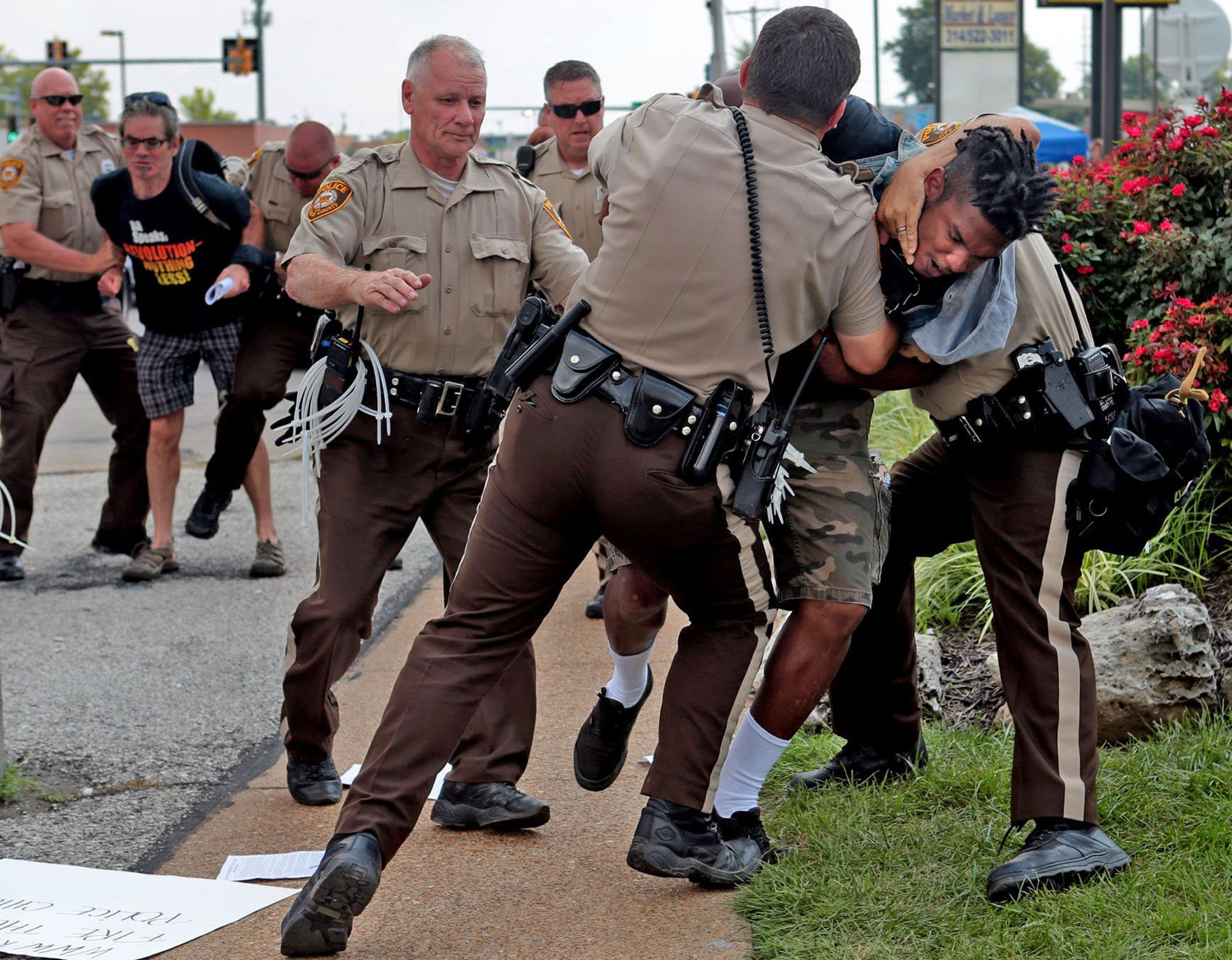 Police tackle a man who was walking down the street in front of McDonald's in Ferguson, Mo. on Aug. 18, 2014.