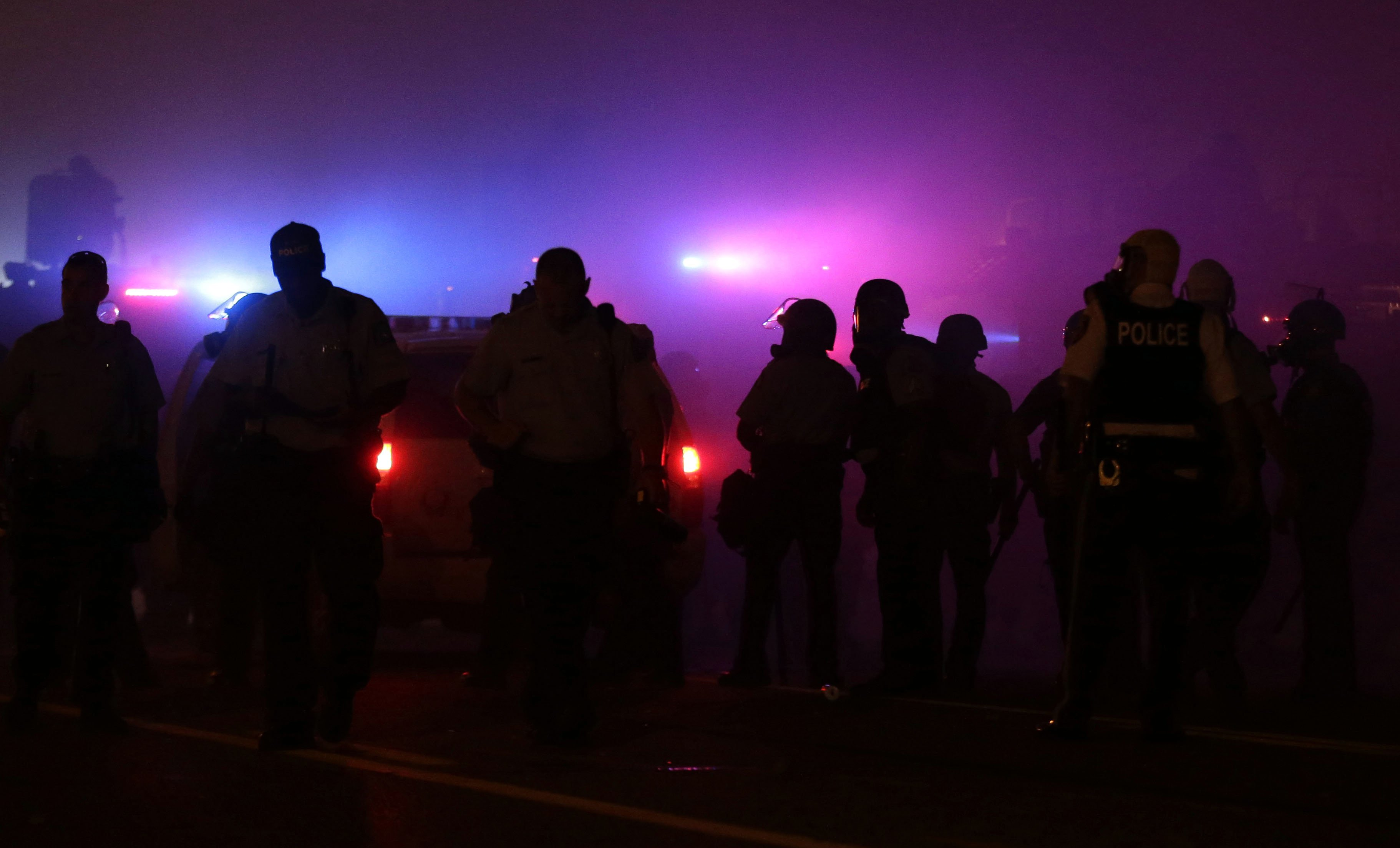 Police wait to advance after tear gas was used to dispersed a crowd in Ferguson, Mo. on Aug. 17, 2014.