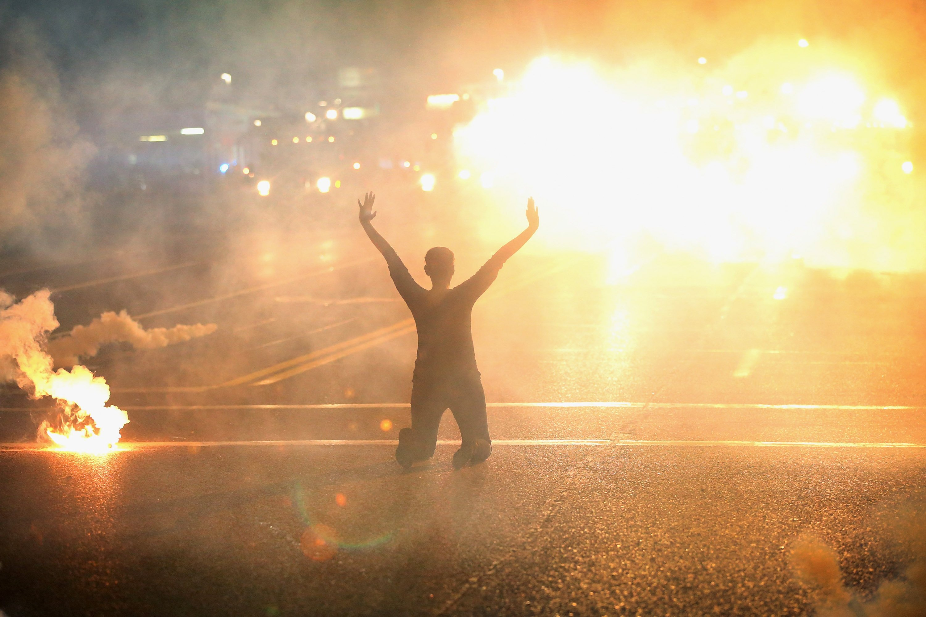 "Tear gas rains down on a woman kneeling in the street with her hands in the air during a demonstration in Ferguson on Aug. 17, 2014. The ""hands up, don't shoot"" pose became the defining gesture of the protests."