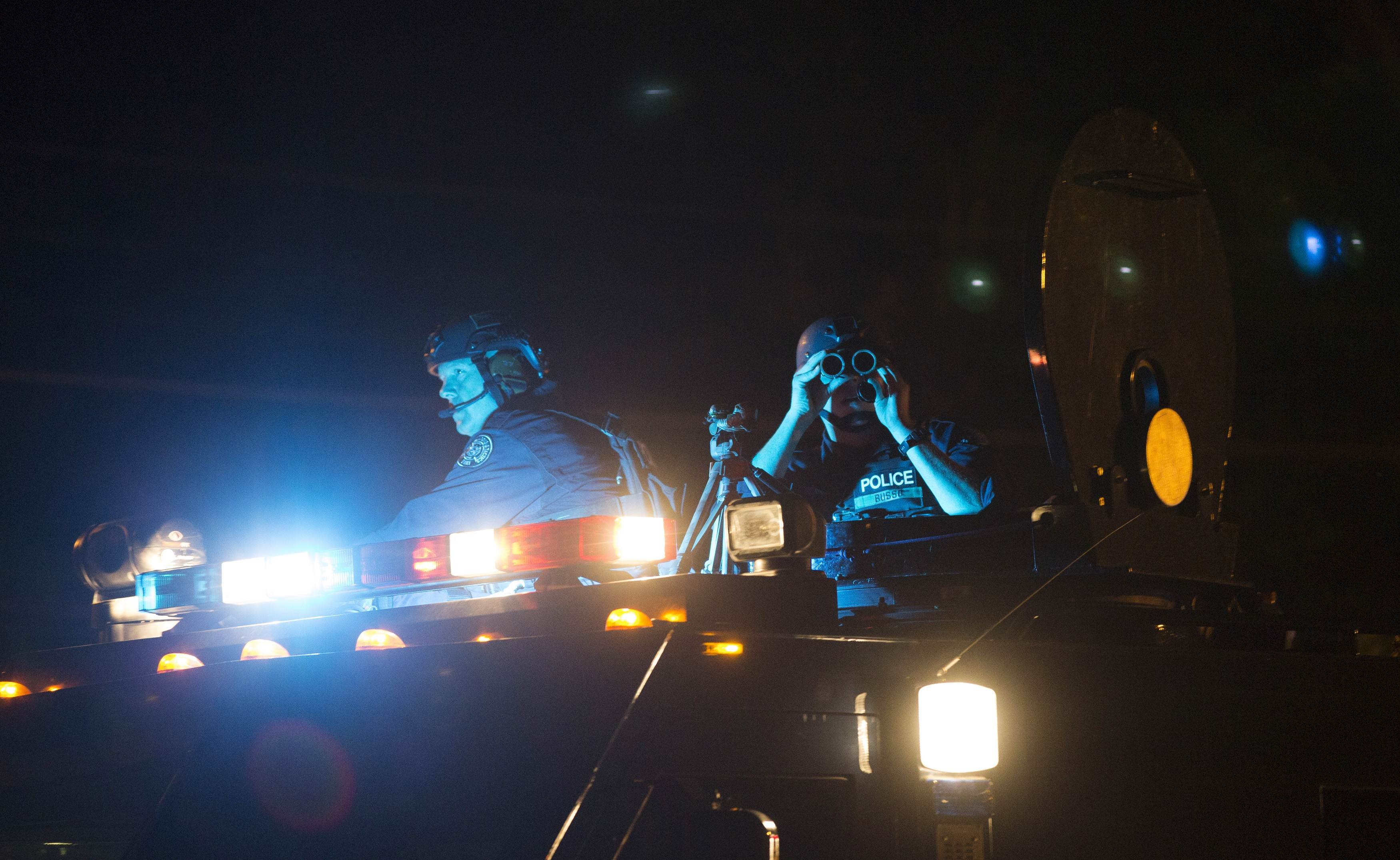 Police officers keep watch from an armored vehicle as they patrol a street in Ferguson, Mo., on Aug. 11, 2014