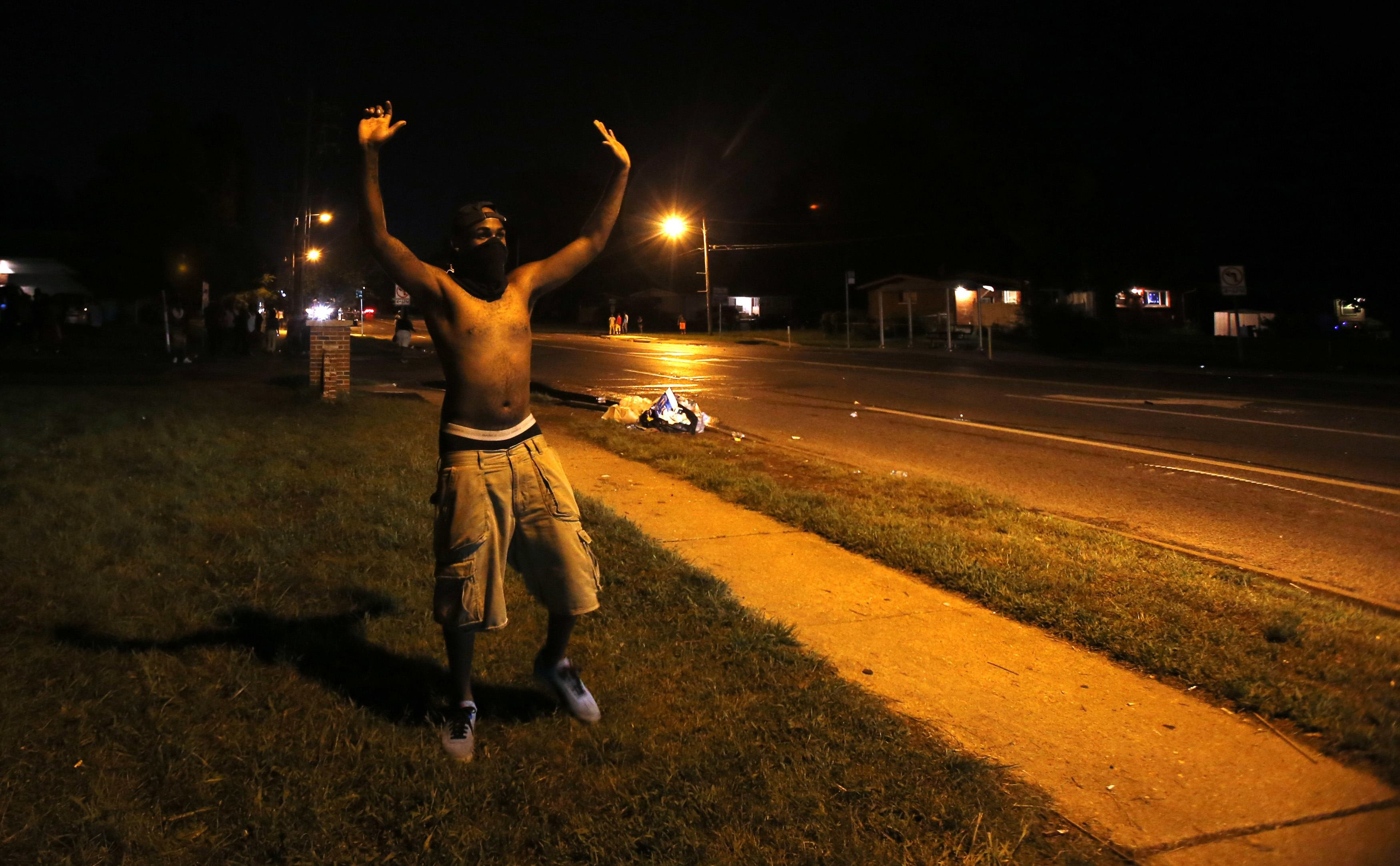 A demonstrator raises his hands in front of of a police officer in Ferguson, Mo. on Aug. 11, 2014.