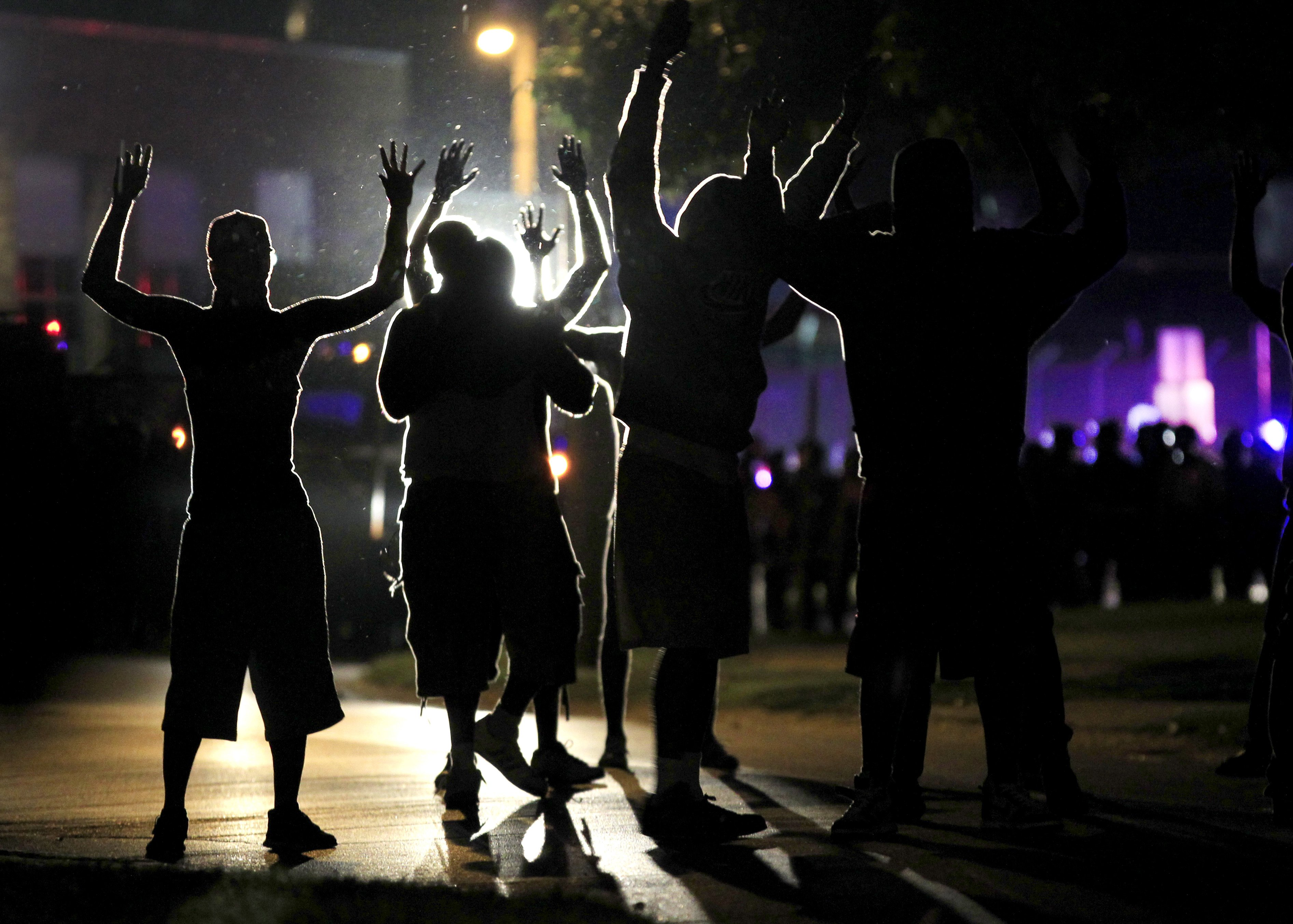 People raise their hands in the middle of the street as riot police move toward their position trying to get them to disperse, in Ferguson, Mo. on Aug. 11, 2014.
