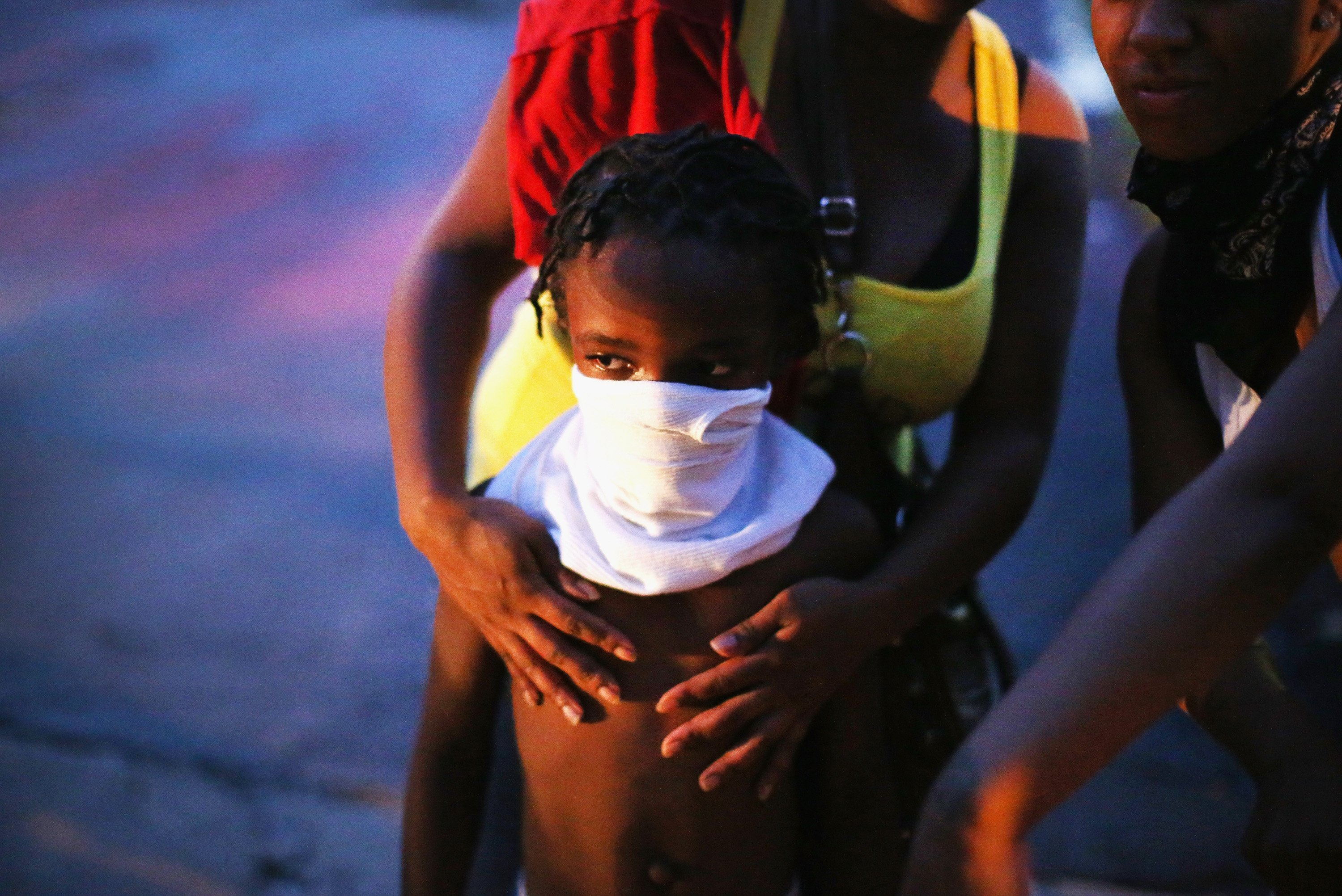 A child uses a rag to shield his face from tear gas fired by riot police, who used it to force protestors from the business district into nearby neighborhoods in Ferguson, Mo. on Aug. 11, 2014.