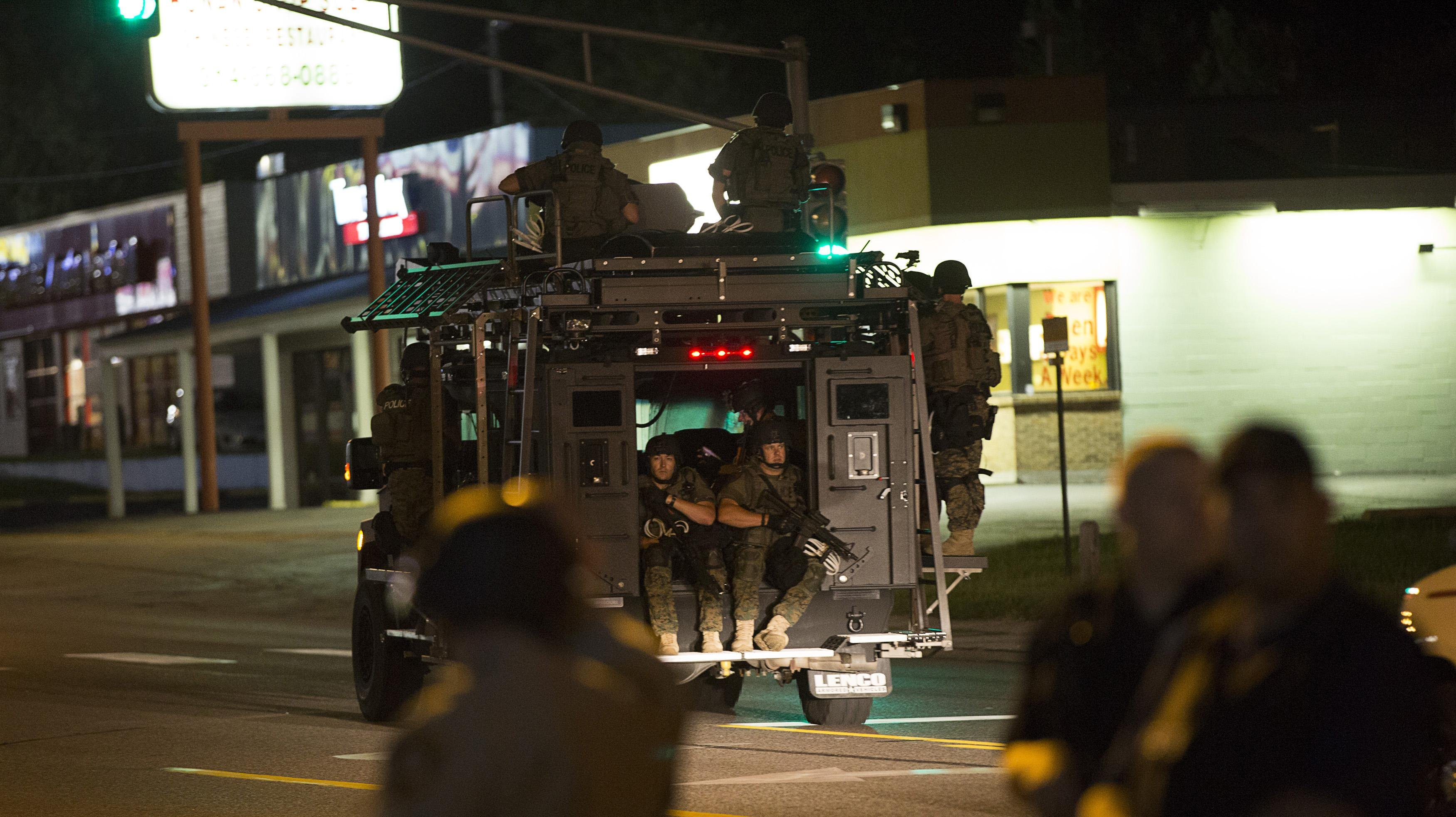 Police officers ride an armored vehicle as they patrol a street in Ferguson, Mo. on Aug. 11, 2014.