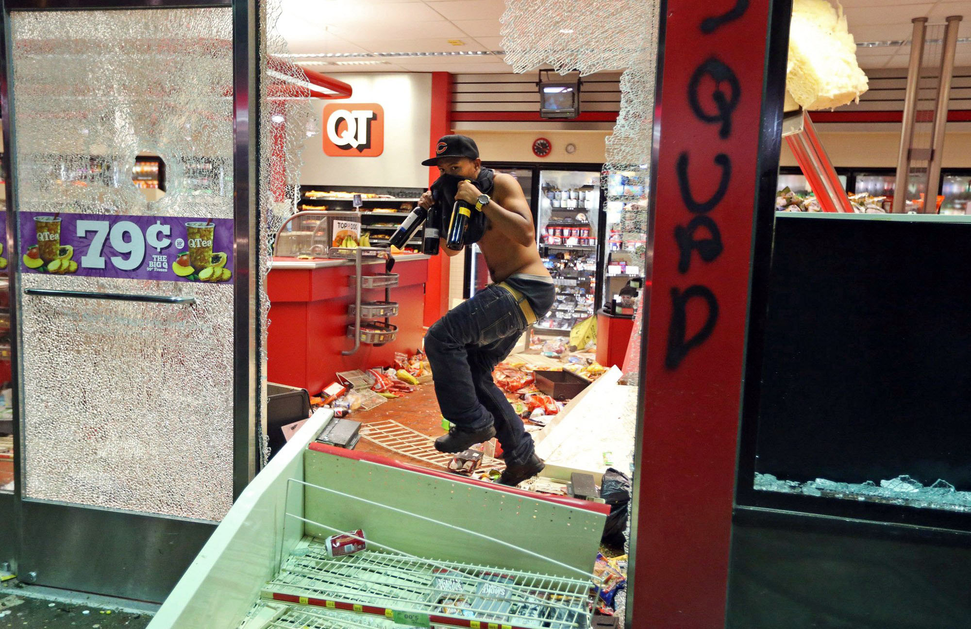A man leaves a store after looting in Ferguson, Mo. on Aug. 10, 2014.