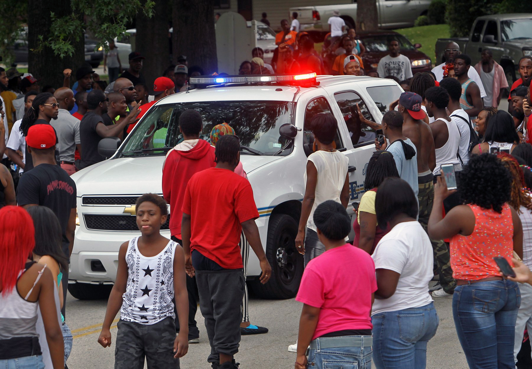 Protesters bang on the side of a police car in Ferguson, Mo. on Aug. 10, 2014.