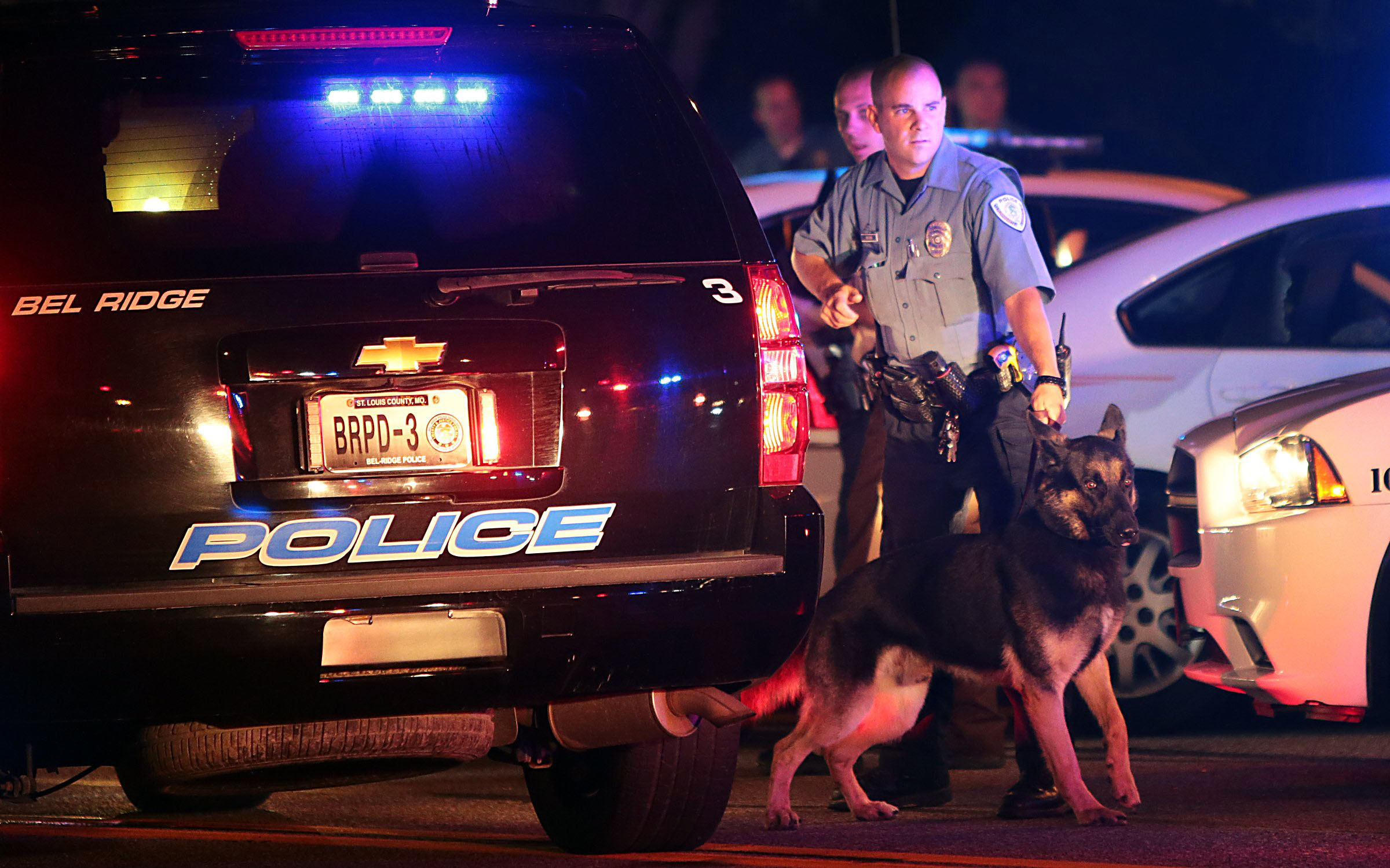 Police officers patrol the area during protests and looting in Ferguson, Mo. on Aug. 10, 2014.
