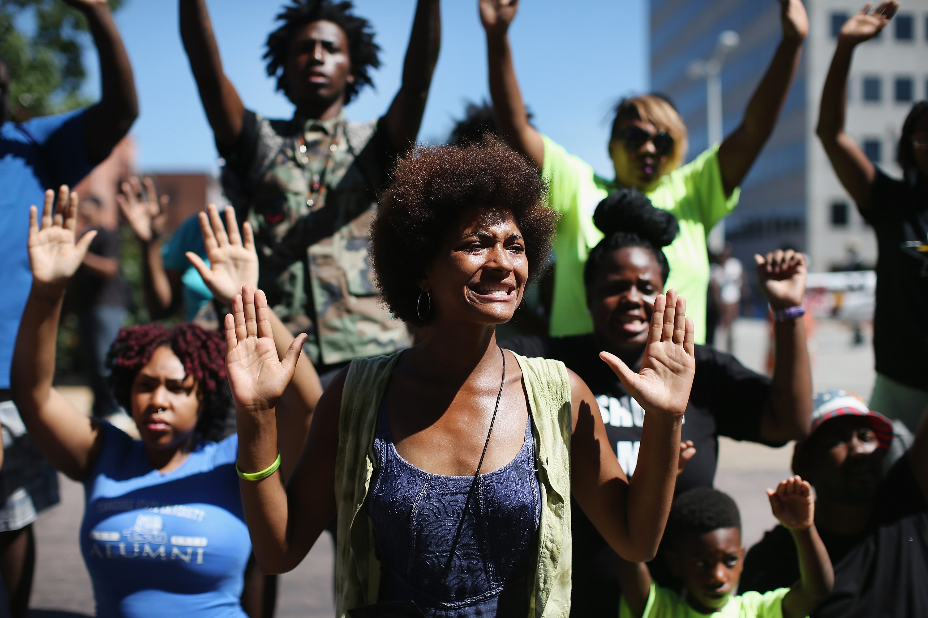 "Demonstrators raise their hands and chant ""hands up, don't shoot"" during a protest over the killing of Michael Brown on in Clayton, Mo. on August 12, 2014."