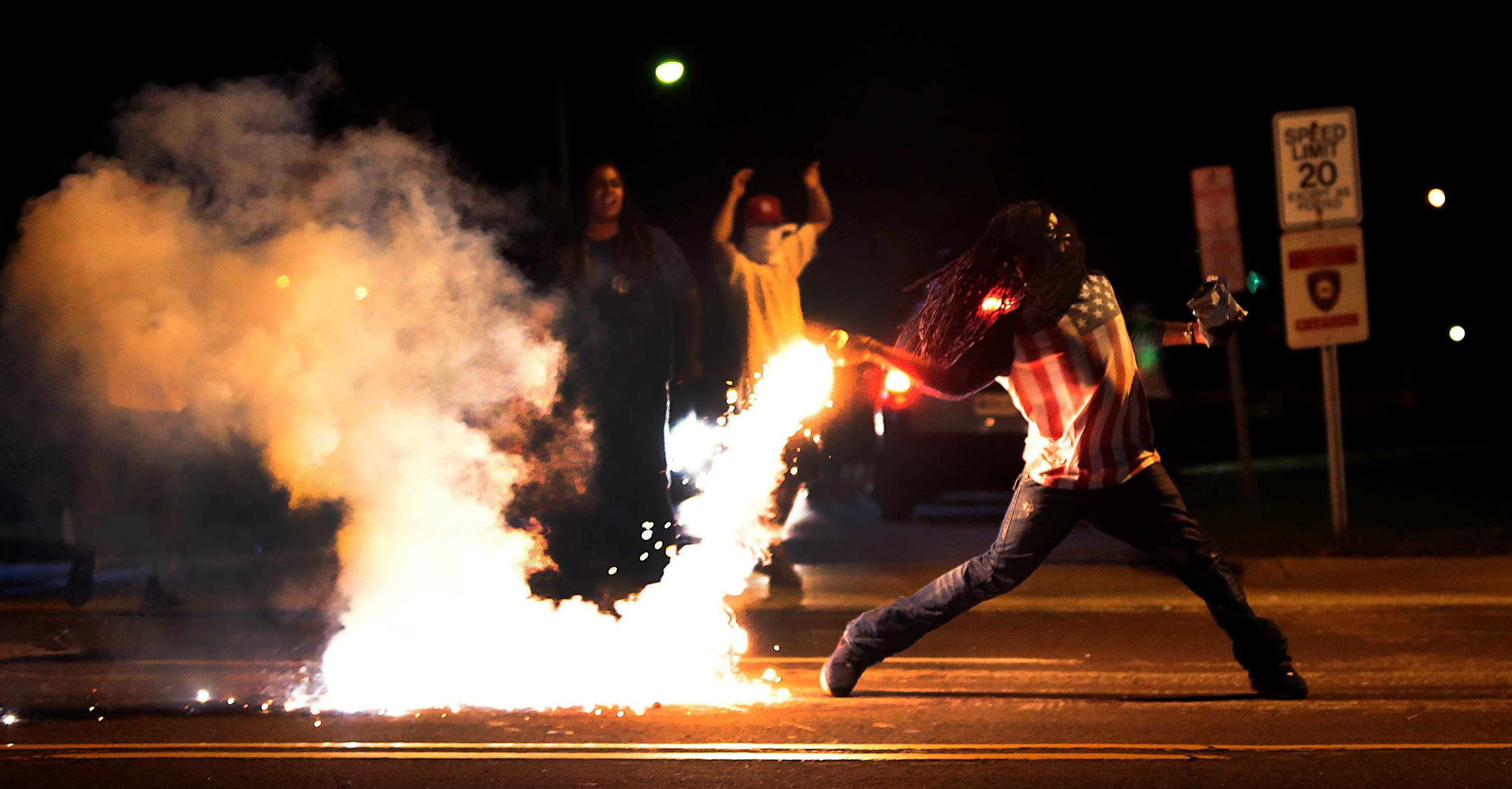 A demonstrator throws back a tear gas container after tactical officers worked to break up a group of bystanders on Chambers Road near West Florissant in Ferguson on  Aug. 13, 2014.