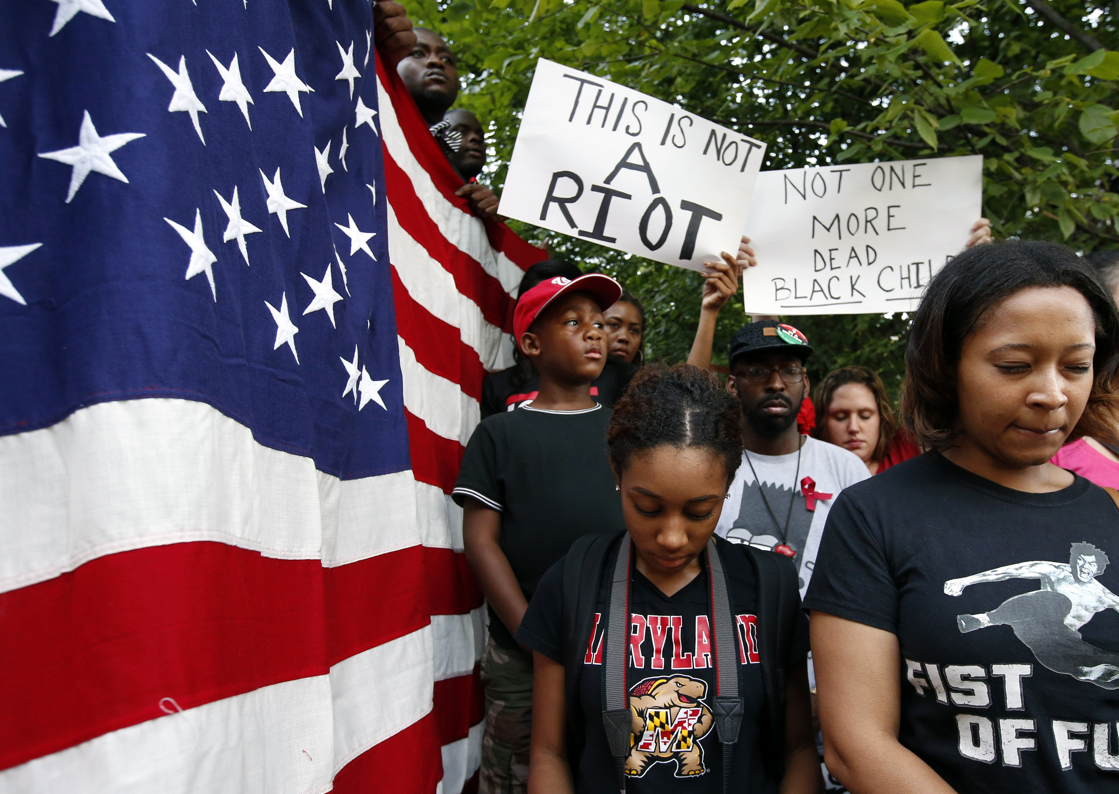 Jordan Johnson, left, 8, from Washington, Camille Chrysostom of Bowie, Md., and Jaimee Swift of Philadelphia, observe a moment of silence at Meridian Hill Park, also known as Malcom X Park, Thursday, Aug. 14, 2014 in Washington, to protest the fatal shooting of Michael Brown by police in Ferguson, Mo.
