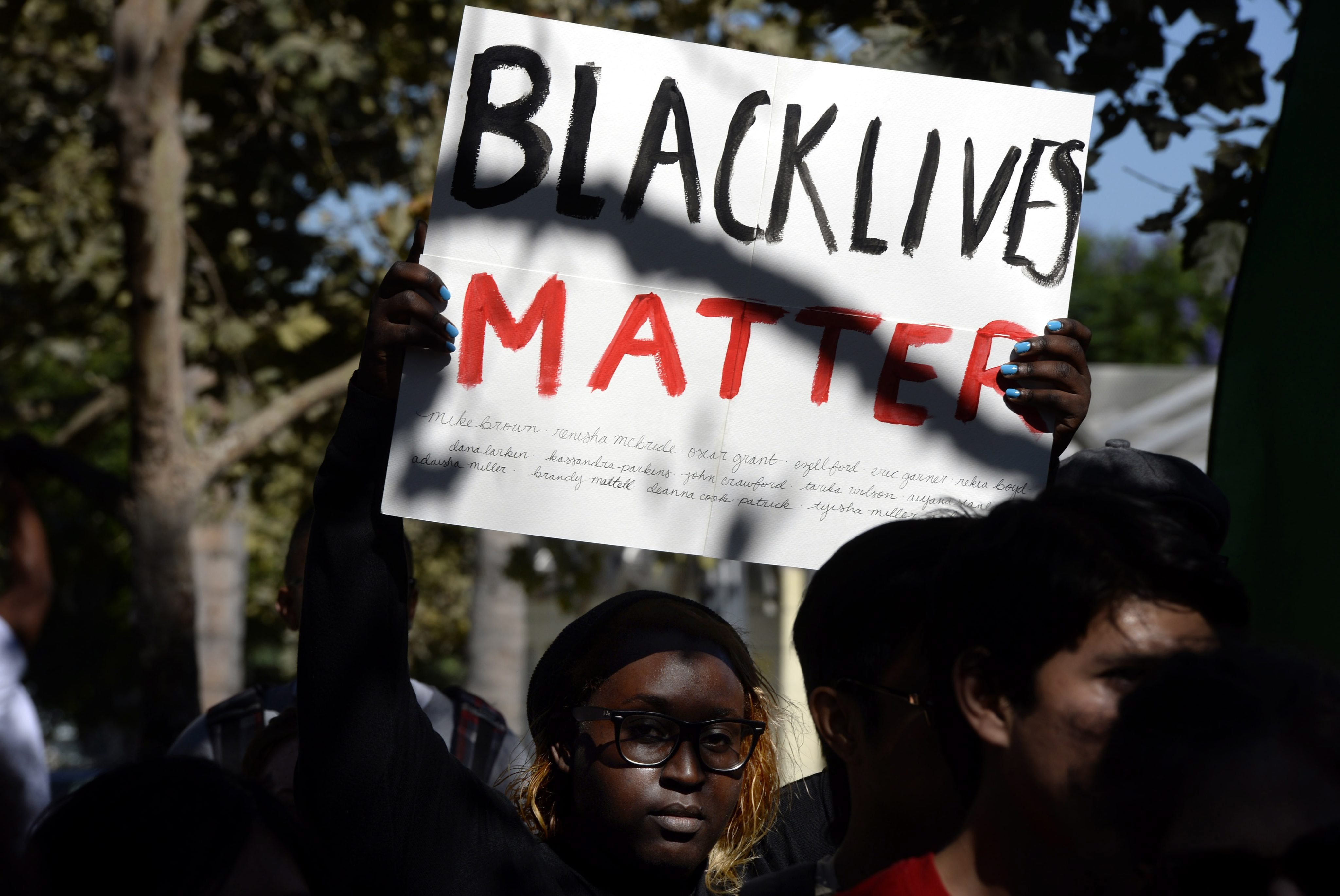 A protestor holds a sign that reads 'Black Lives Matter' as she joins hundreds of demonstrators who gathered in Leimert Park in South Central Los Angeles, California, USA, 14 August 2014, to protest the police shooing of Mike Brown in Missouri.