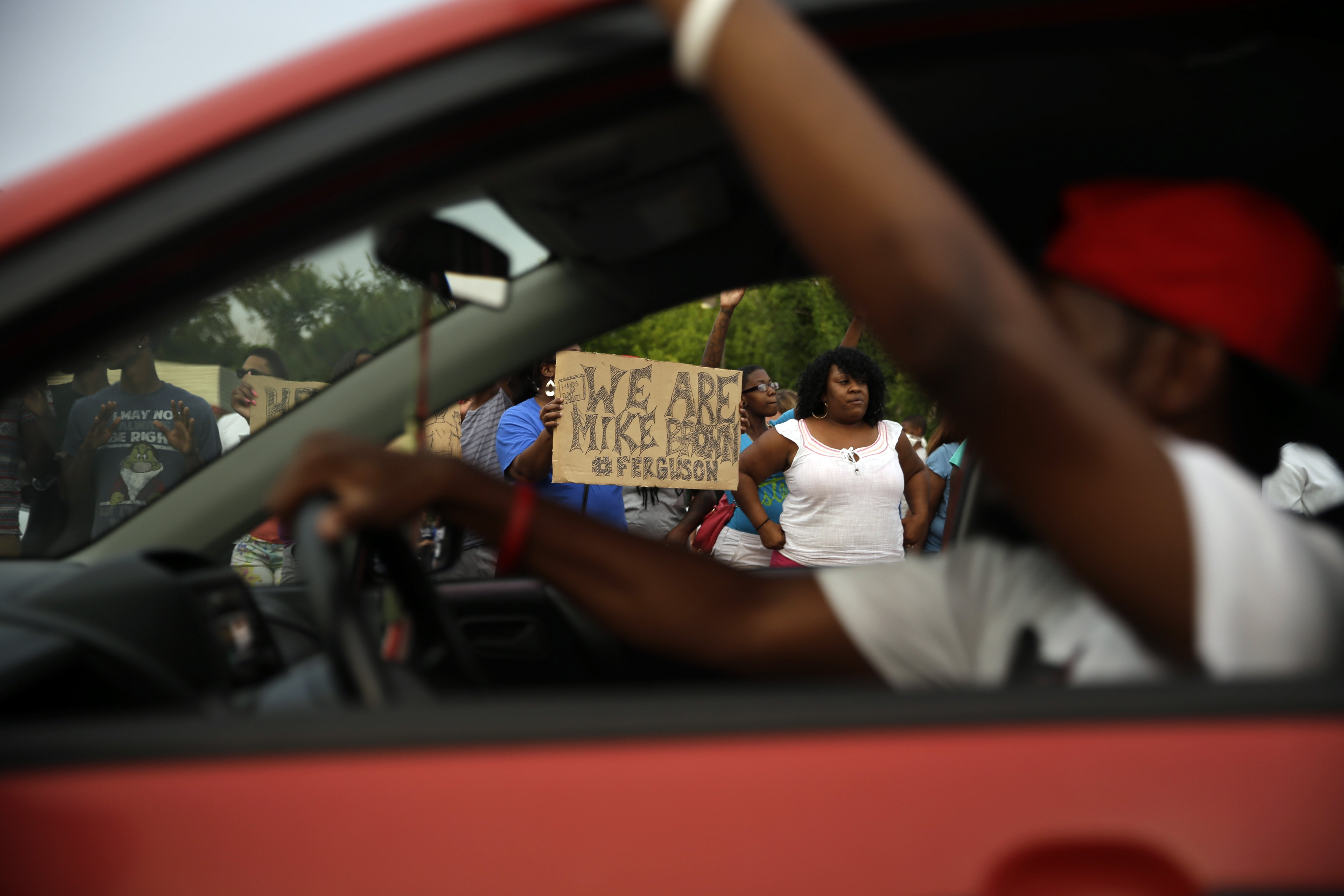 Demonstrators hold signs as traffic slowly moves past Thursday, Aug. 14, 2014, in Ferguson, Mo. Hundreds of people protesting the death of  Michael Brown marched through the streets of Ferguson alongside state troopers Thursday.