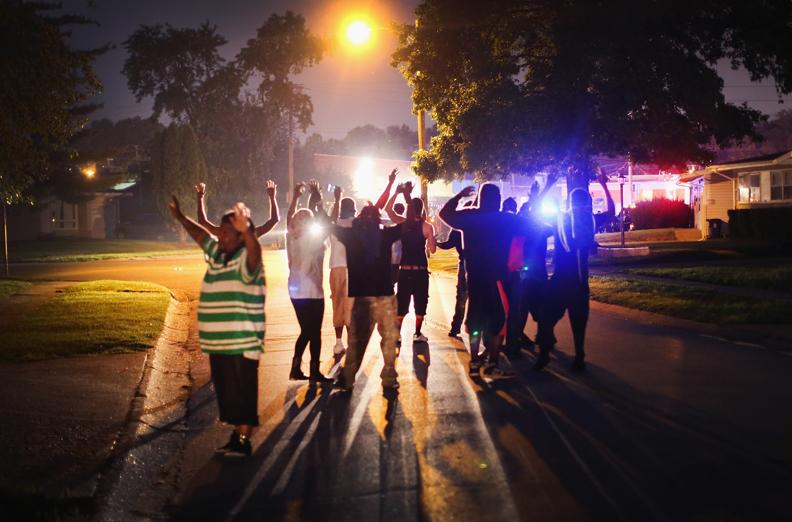 With their hands raised, residents gather at a police line as the neighborhood is locked down following skirmishes on August 11, 2014 in Ferguson, Missouri.