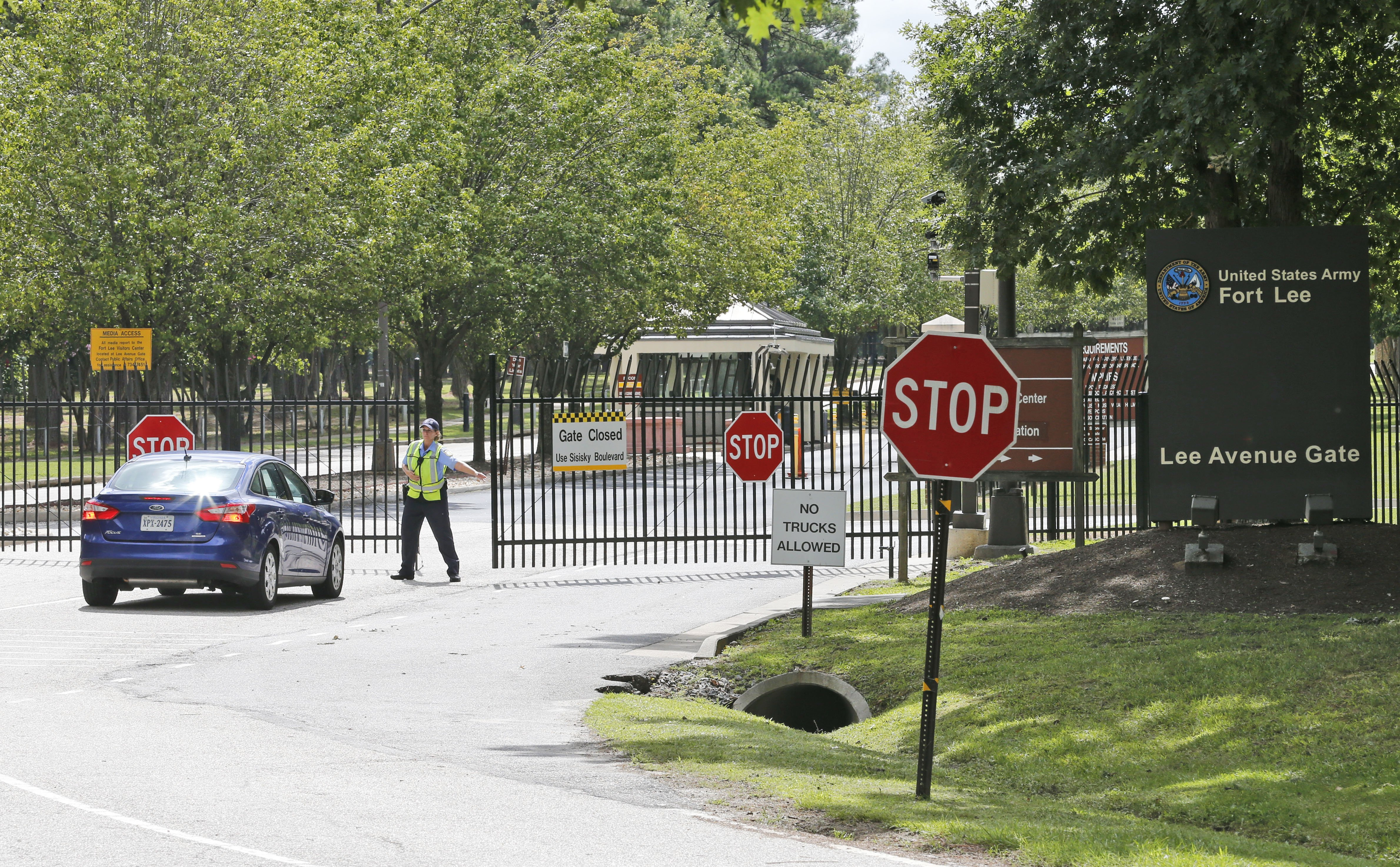 Security guards open a gate for motorist at the visitor entrance to Fort Lee, Va. on Aug. 25, 2014.