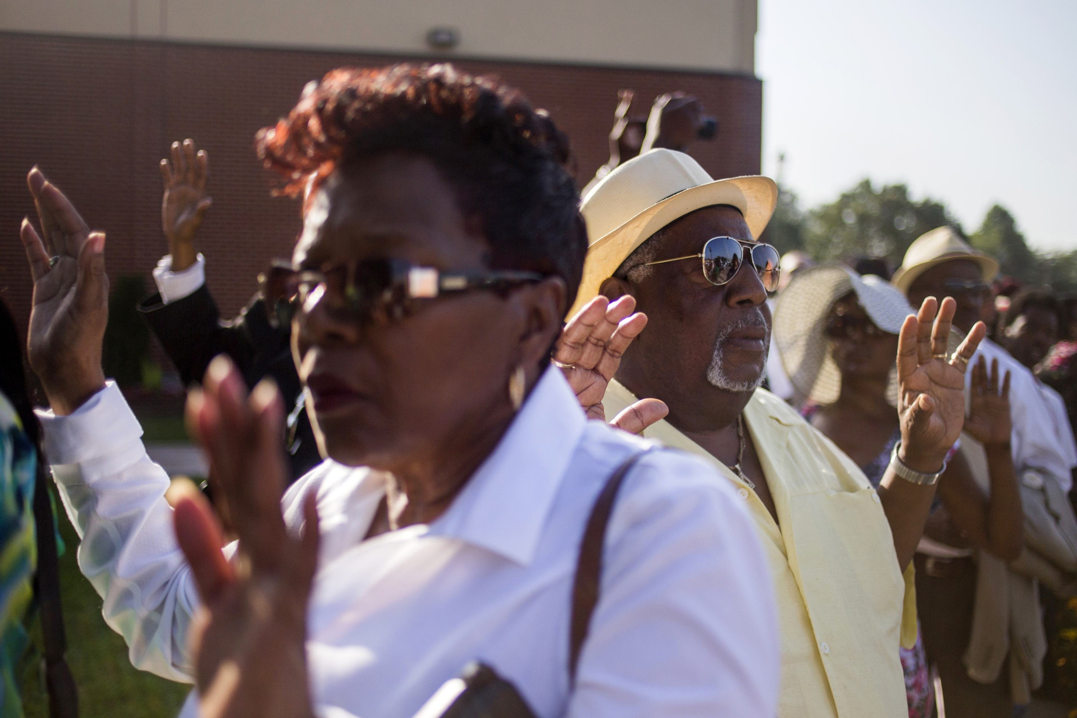 "Attendees hold their hands up as some chant ""Hands up don't shoot,"" while they wait in line to take part in the funeral services for 18-year-old Michael Brown at the Friendly Temple Missionary Baptist Church in St. Louis, on Aug. 25, 2014."