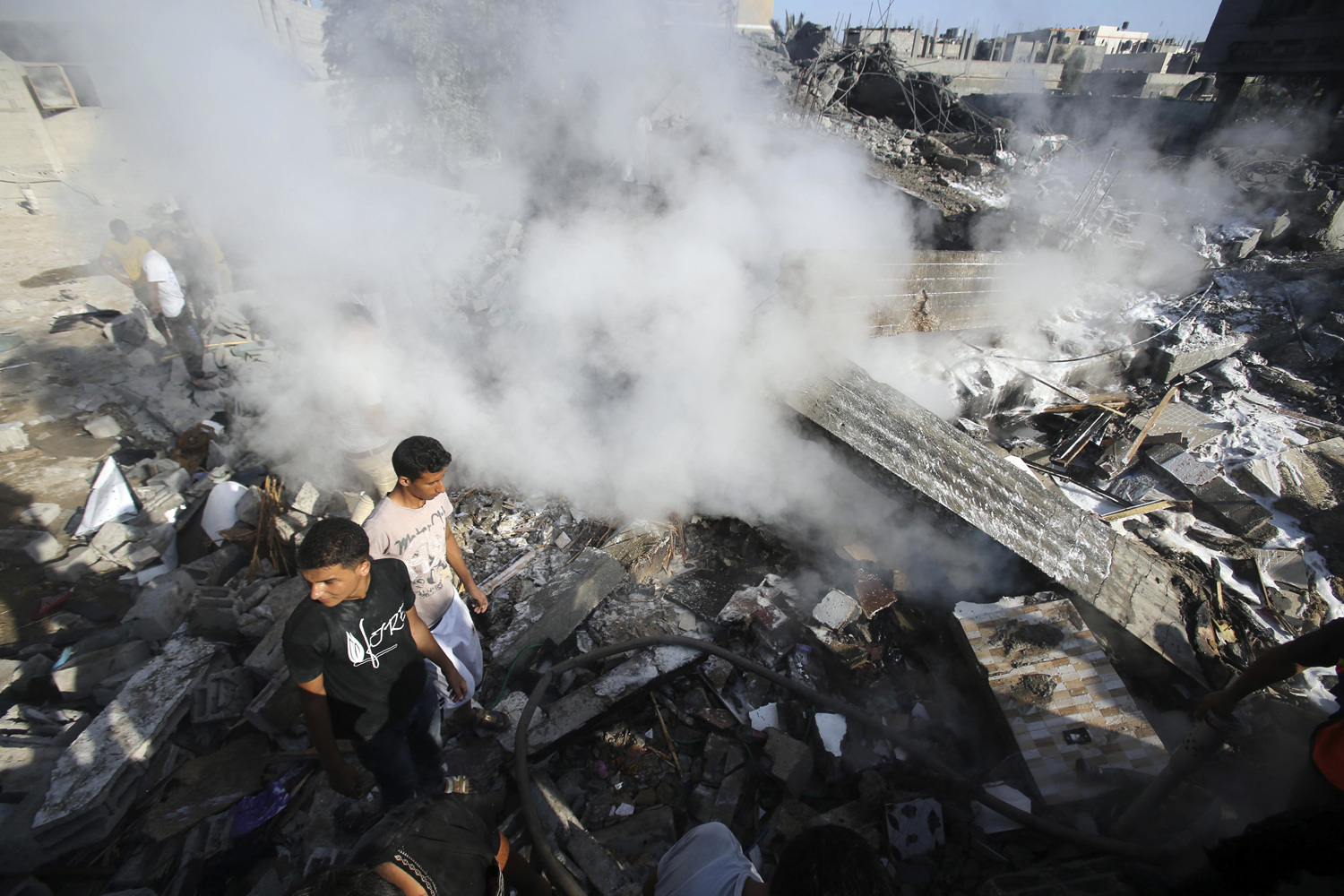 Palestinians stand atop the rubble of a house, which witnesses said was destroyed in an Israeli air strike, in Rafah in the southern Gaza Strip on August 20, 2014.
