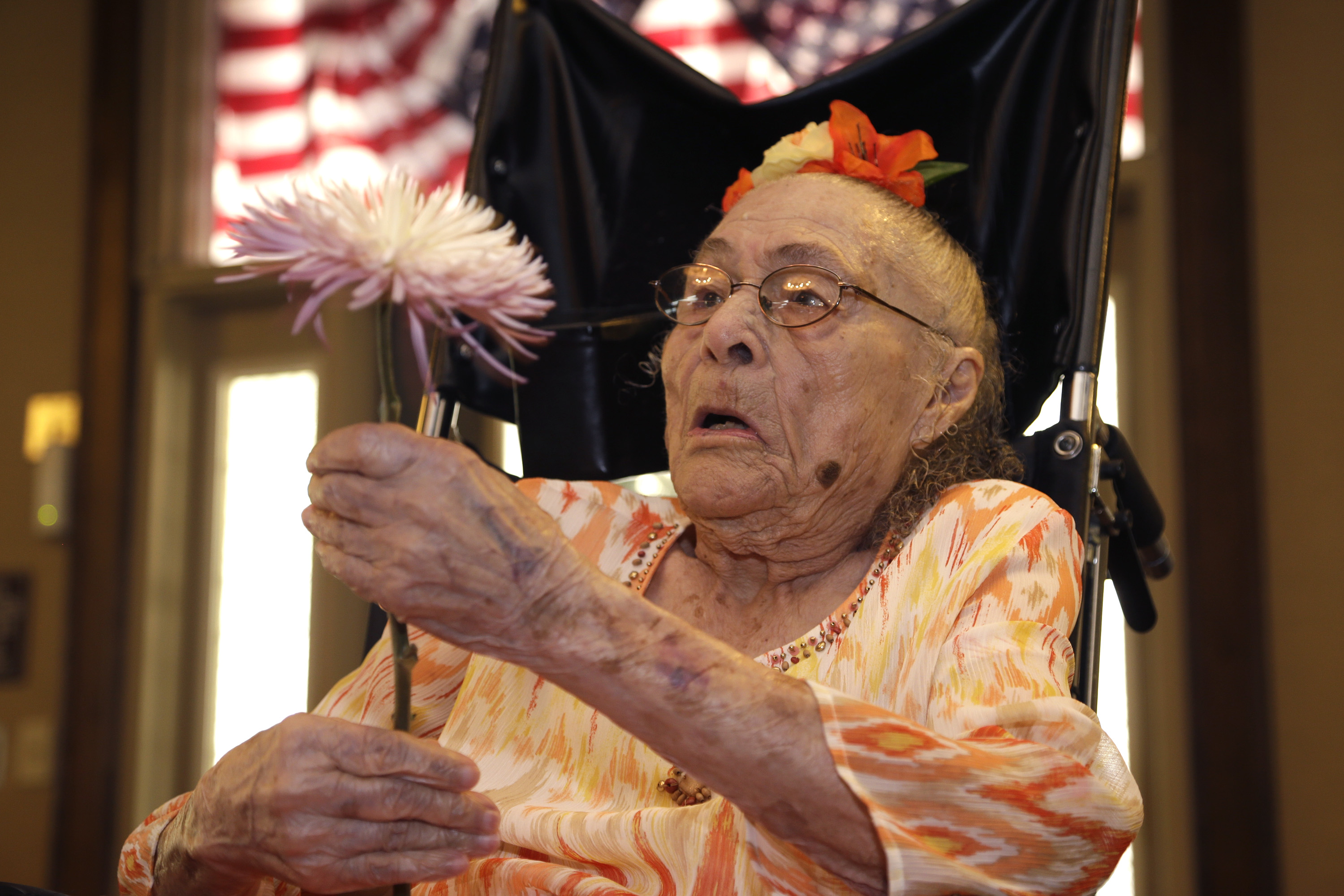 Gertrude Weaver holds a flower given to her a day before her 116th birthday, at Silver Oaks Health and Rehabilitation Center in Camden, Ark., July 3, 2014.  The Gerontology Research Group says Weaver is the oldest person in the United States and second-oldest person in the world.