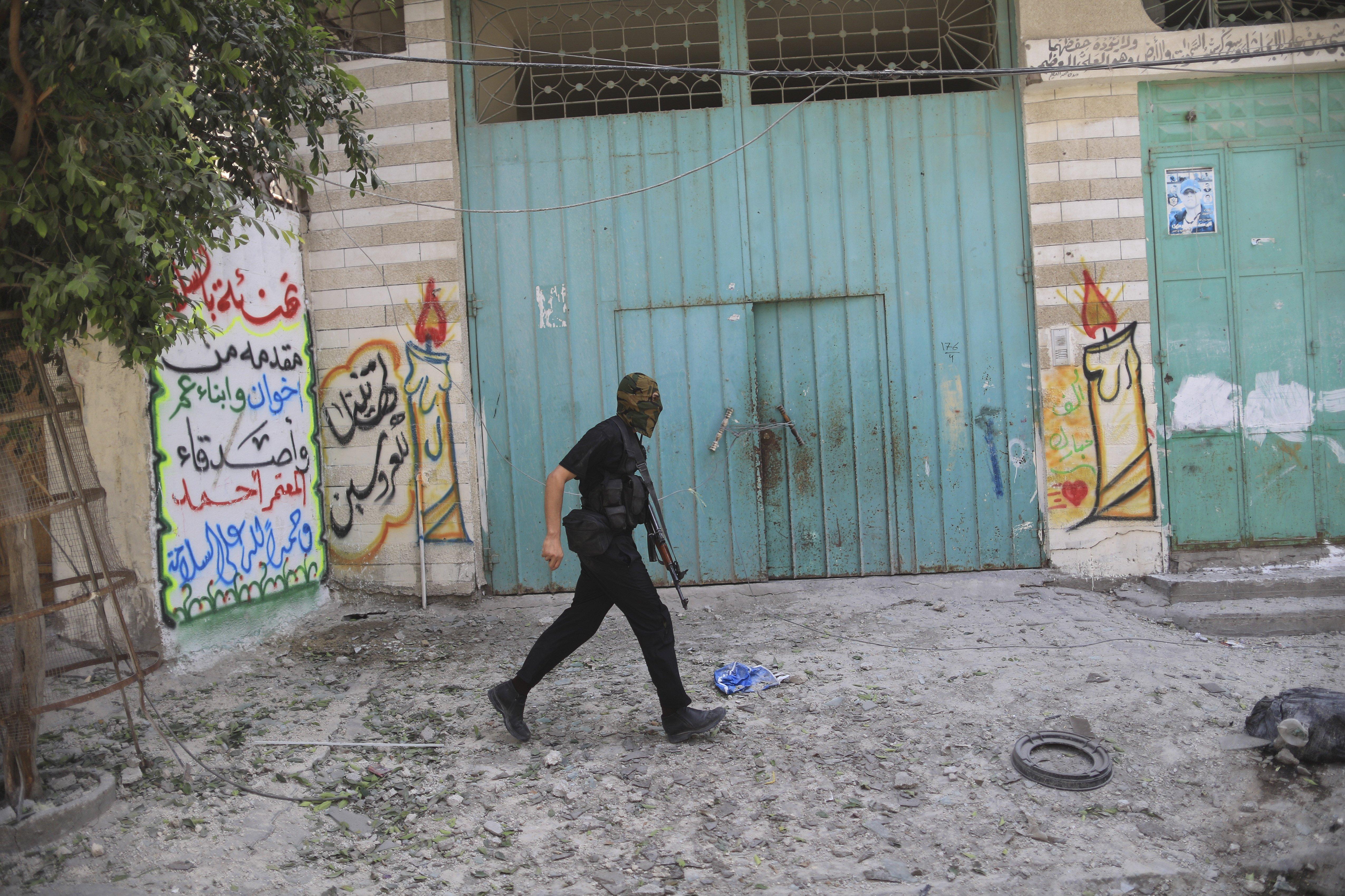 An armed Hamas militant walks through a street in the Shejaiya neighborhood of Gaza City on July 20, 2014.