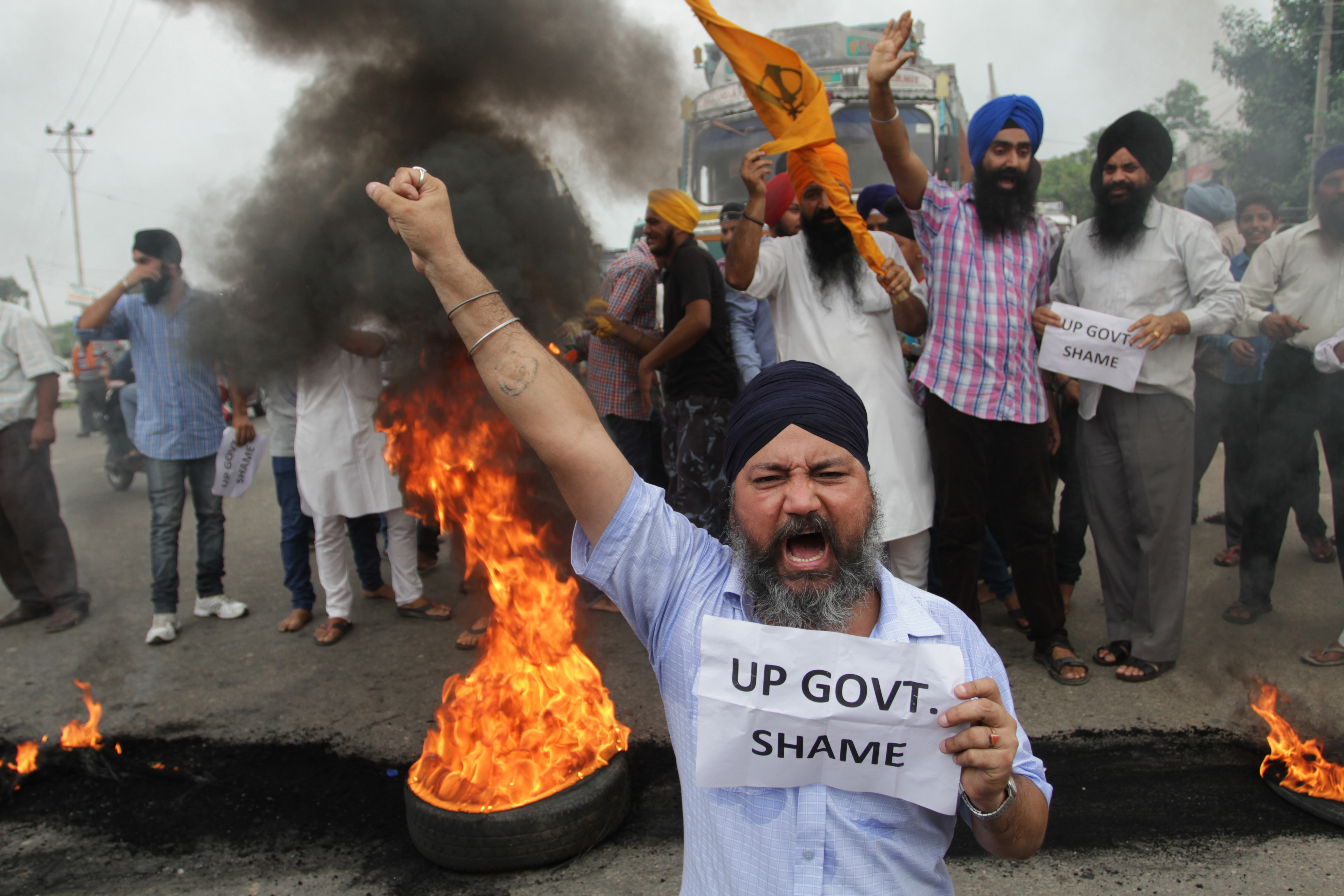 Members of the Sikh community shout slogans as they burn tires during a protest in the Indian state of Uttar Pradesh on July 27, 2014.