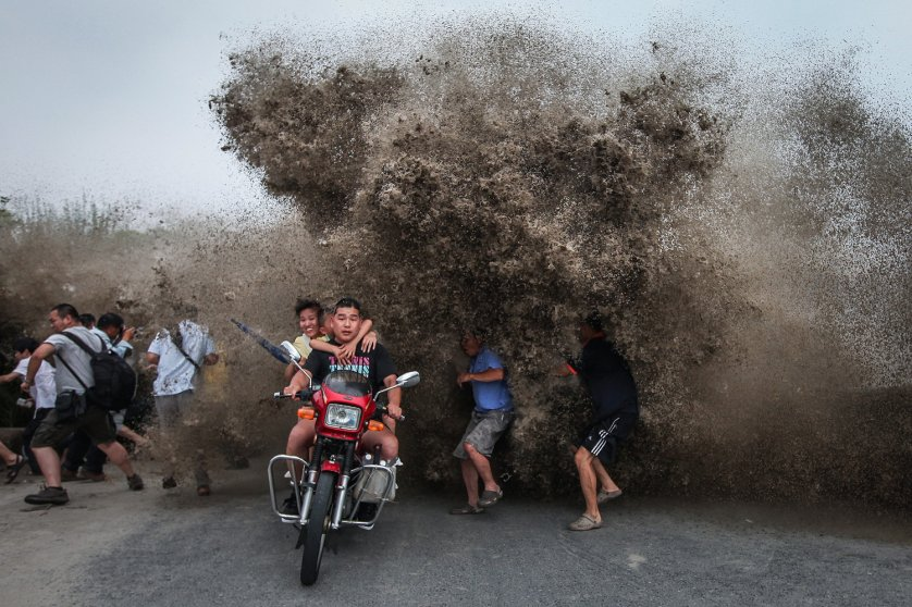 Tidal wave spectators react to a high wave hitting the bank of Qiantang River in Hangzhou, Zhejiang province, China on August 13, 2014.