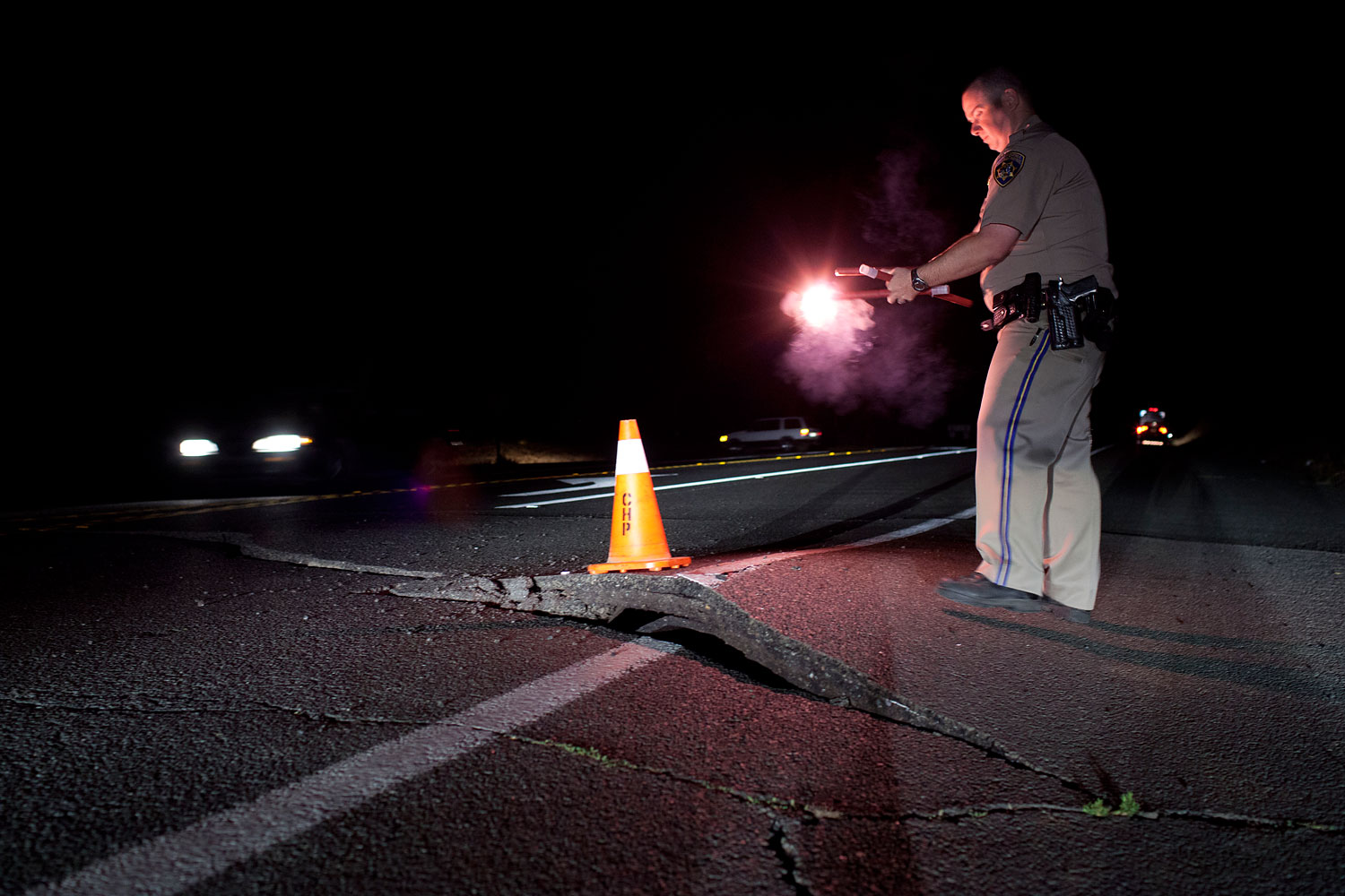 A California Highway Patrol officer redirects traffic from a buckled section of California's Highway 12 near Sonoma, Calif.