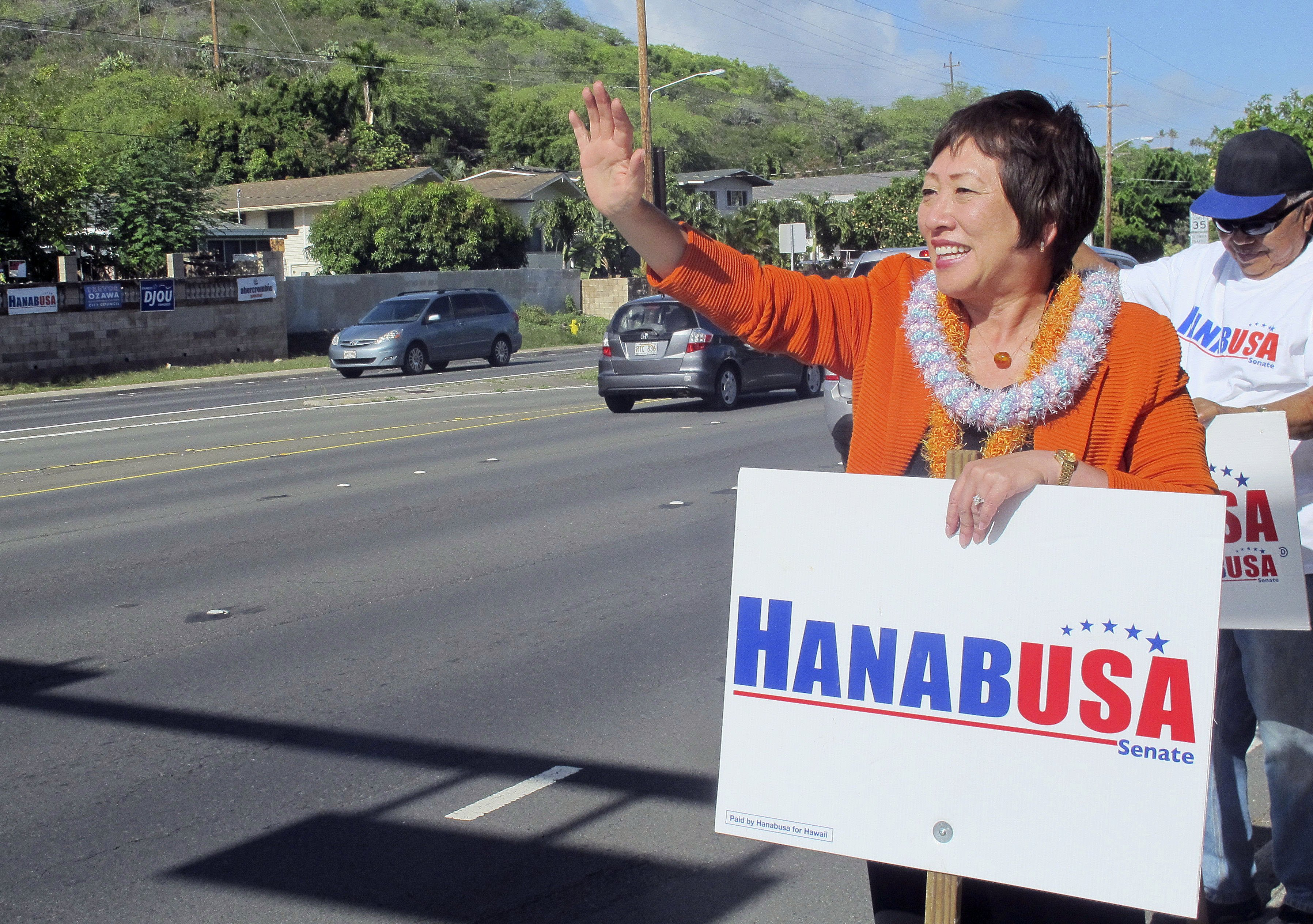 U.S. Rep. Colleen Hanabusa waves at drivers while campaigning for U.S. Senate in Honolulu on Aug. 4, 2014.