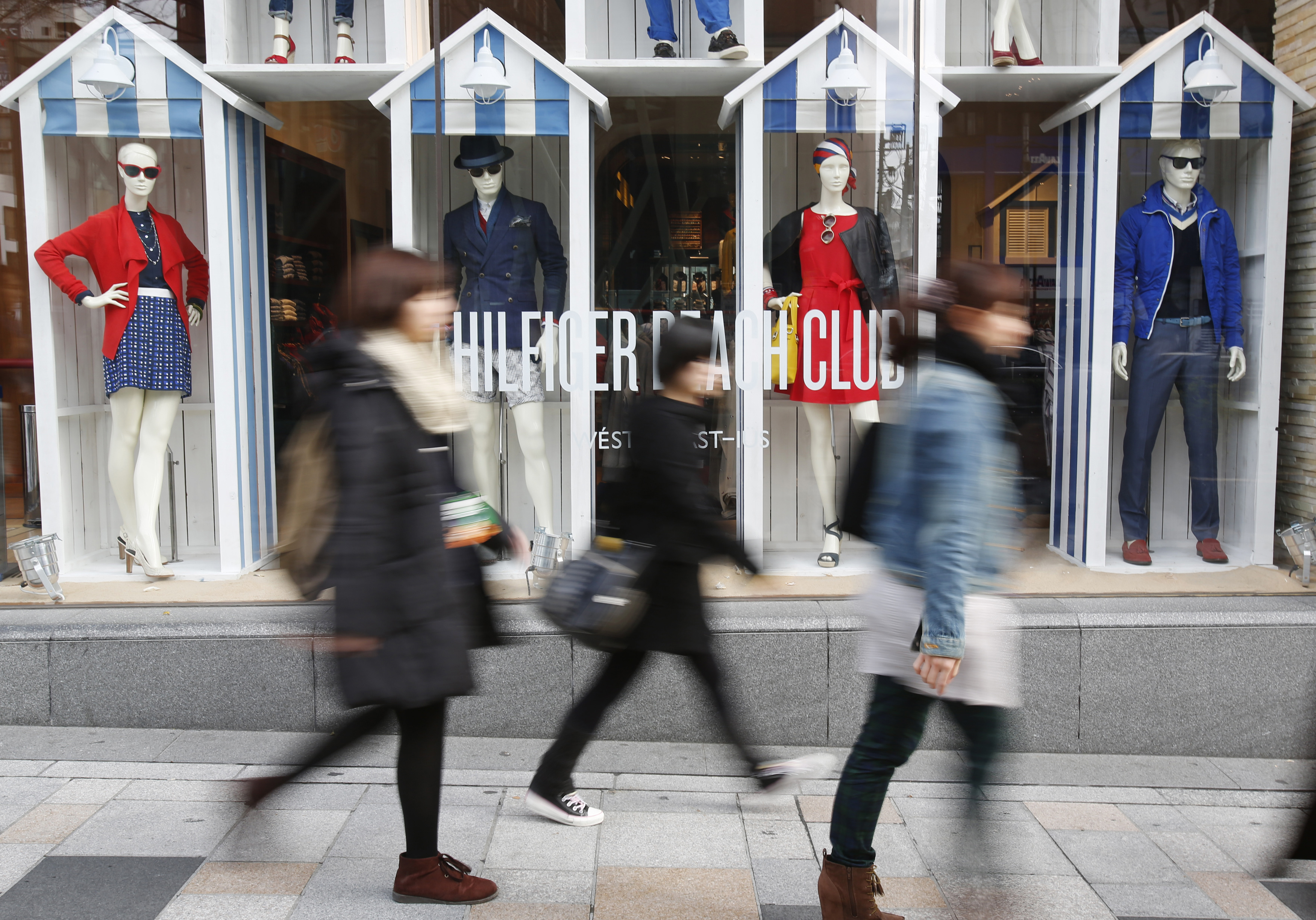 Pedestrians walk past a show window of a clothing store at Harajuku shopping district in Tokyo February 28, 2014.