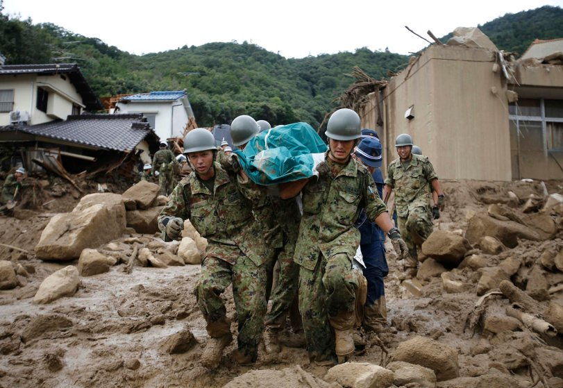 Japan Self-Defense Force soldiers and police officers carry the body of a victim in a plastic bag at a site where a landslide swept through a residential area at Asaminami ward in Hiroshima, western Japan, Aug. 20, 2014.