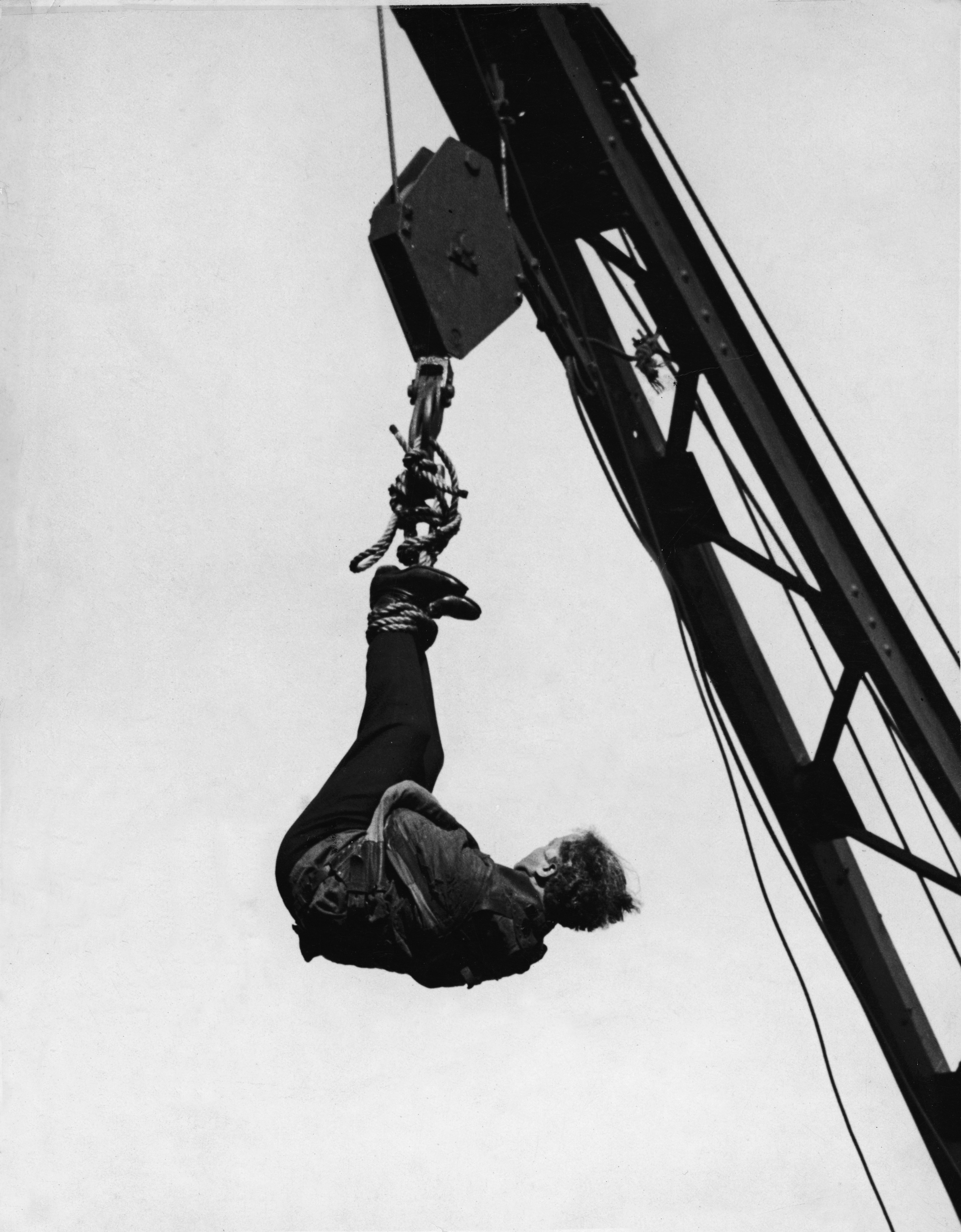 Houdini wears a straitjacket and hangs from a crane during one of his escape acts over Broadway and 46th Street, Manhattan, New York.